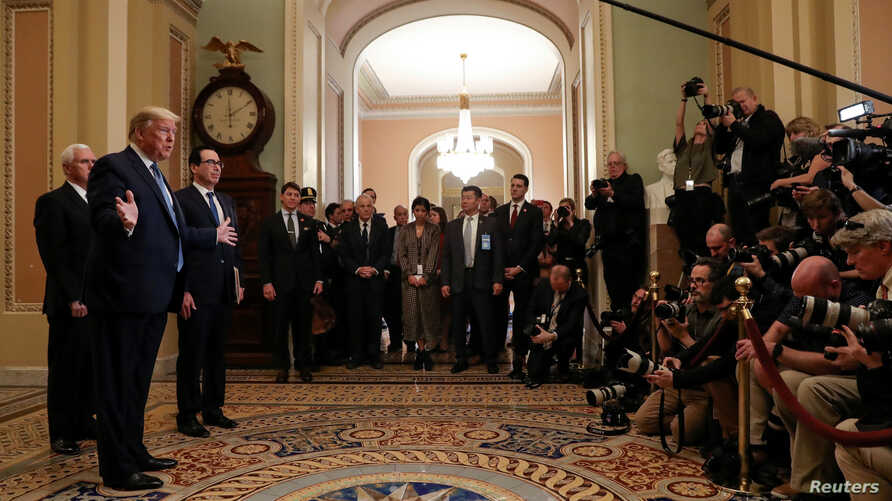 U.S. President Donald Trump is flanked by Vice President Mike Pence and Treasury Secretary Steven Mnuchin as he speaks to…
