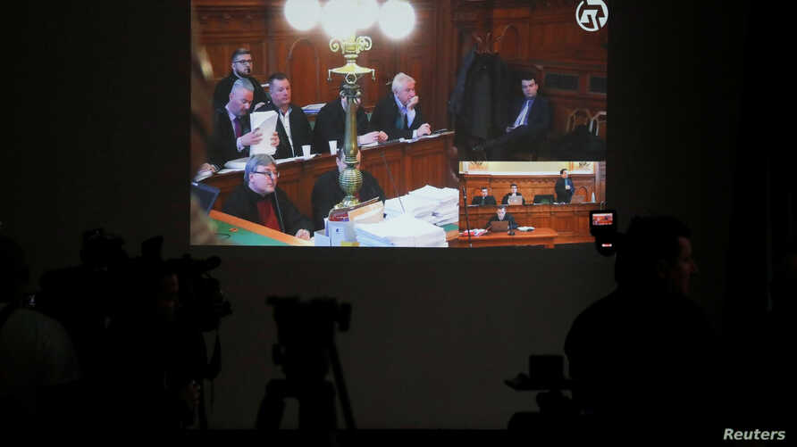 Journalists watch prosecutors and court officials on a screen as a live feed is transmitted during a trial of the Ukrainian…