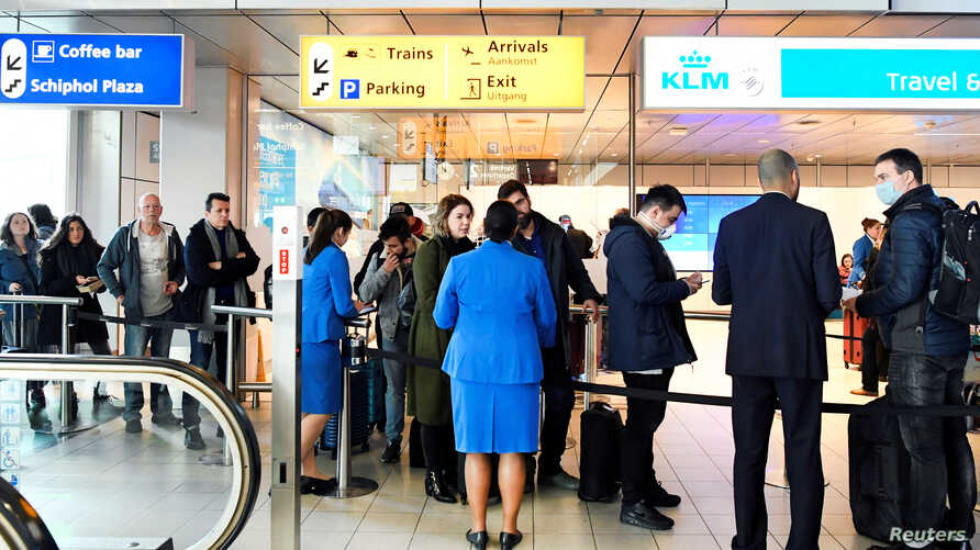 Travelers wait to be informed in the departure hall at the KLM Service Desk, as the travel ban for European countries announced…