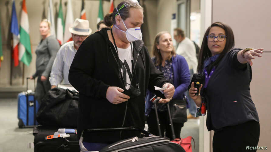 FILE PHOTO: A ticket agent helps travelers arriving on a flight from Frankfurt, Germany before travel restrictions are enacted…