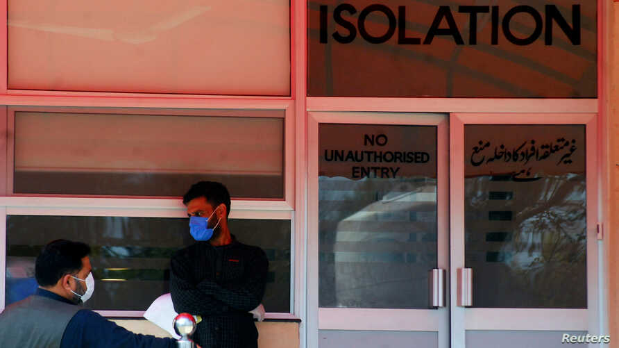Men wear protective mask as a preventive measure against coronavirus, as they stand outside the Isolation ward at the Pakistan…