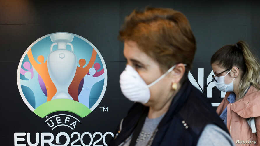 Travellers pass by a logo of the 2020 UEFA European Football Championship displayed on a wall inside Bucharest Henri Coanda…