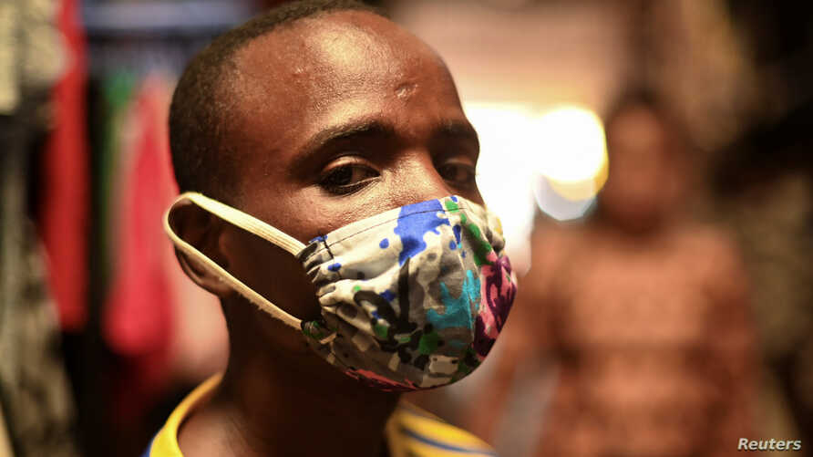 """Eugene Amuri, a vendor at the Kimironko market wears a handmade """"kitenge"""" cloth mask as he attempts to protect against the…"""