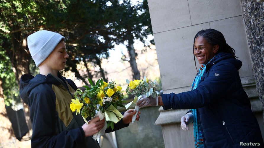Residents collect Posies to hand out for Mother's Day outside St Leonard's Church for Mother's Day as the spread of the…