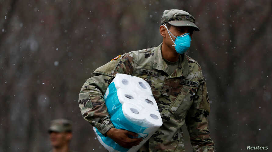 A member of Joint Task Force 2, composed of soldiers and airmen from the New York Army and Air National Guard, wears a face…