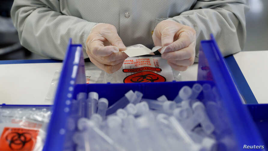 A technician assembles coronavirus test kits at Evolve manufacturing facility, where they will be manufacturing ventilators, in…