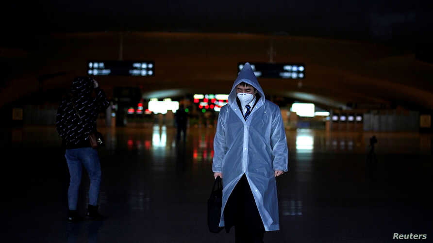 A man wearing a face mask and a plastic raincoat is seen at a railway station of Wuhan on the first day of inbound train…