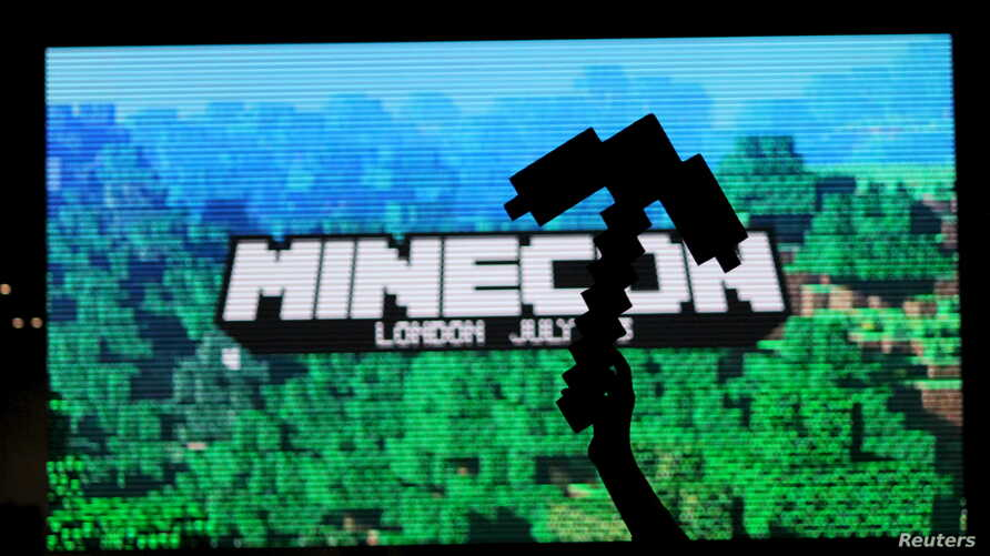 A fan of video game Minecraft waves a foam pick-axe in front of a screen display at the Minecon convention in London July 4,…