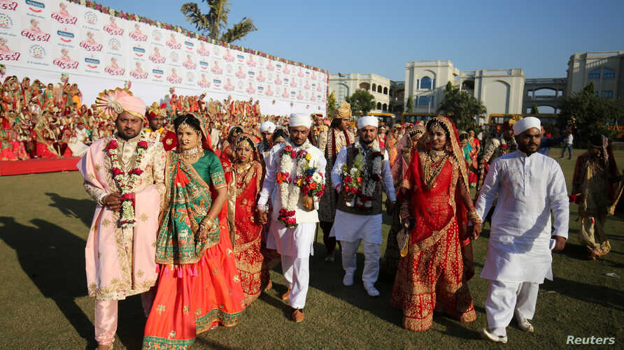 Brides and grooms arrive to take their wedding vows during a mass marriage ceremony, organized by a diamond merchant, in which…