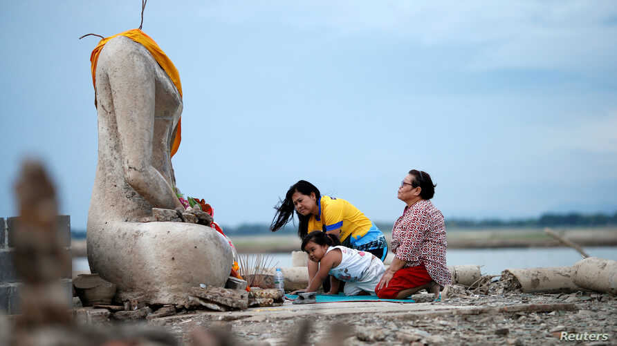 A family prays near the ruins of a headless Buddha statue, which has resurfaced in a dried-up dam due to drought, in Lopburi,…
