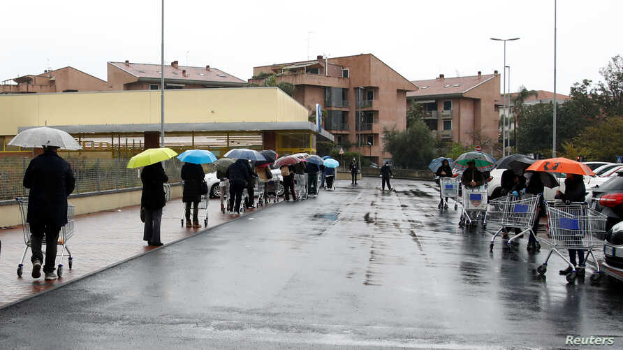 People line up in the rain outside a supermarket after the Italian island of Sicily closed them on Sunday, as it tightens…