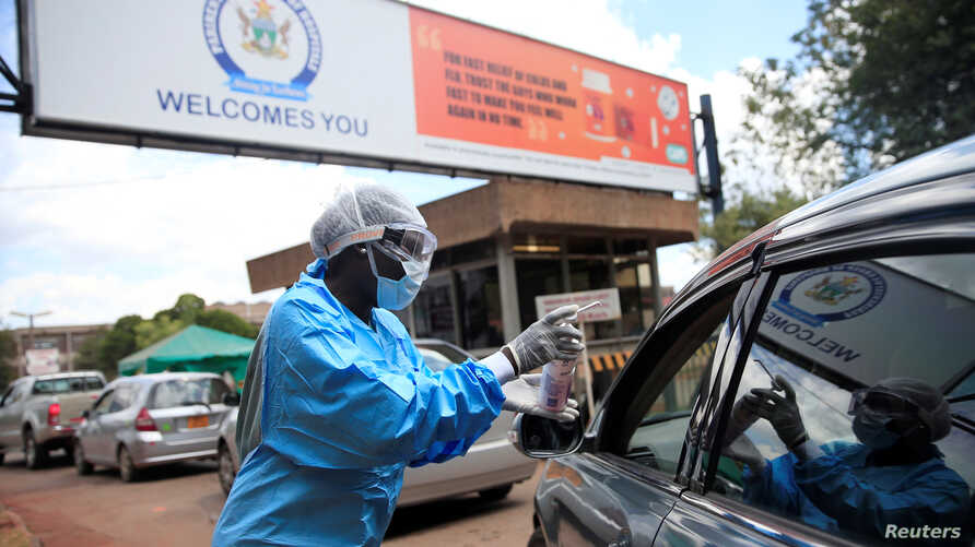 A health worker screens and sanitises visitors to prevent the spread of coronavirus disease (COVID-19) outside a hospital in…