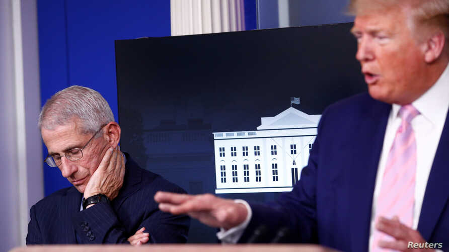Dr. Anthony Fauci, director of the National Institute of Allergy and Infectious Diseases, listens as U.S. President Donald…