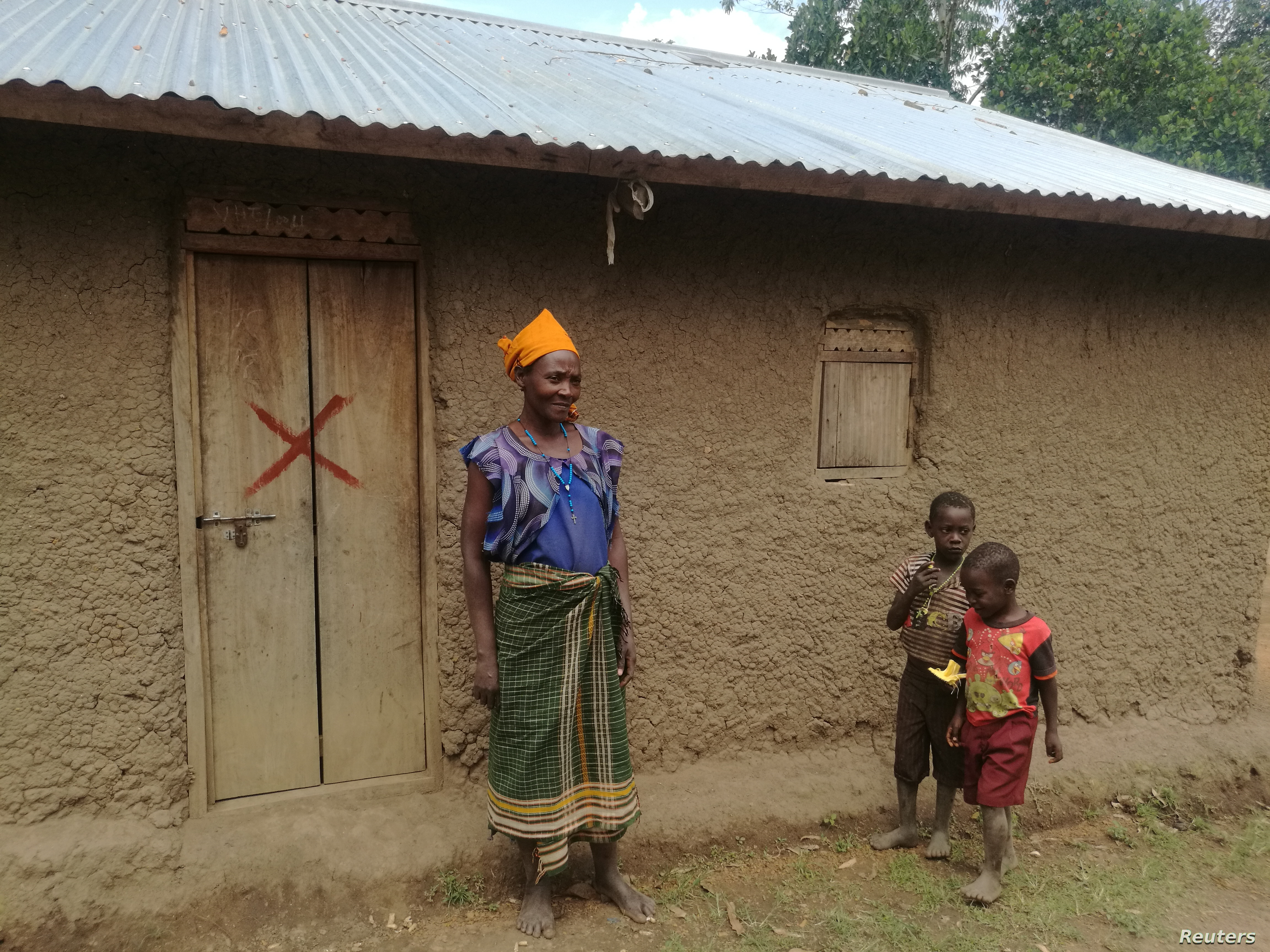 Jacinta Kyomukama and her grandchildren stand in front of her house marked for demolition for an oil pipeline in Kyakatemba village, Hoima District, Uganda, July 14, 2018.