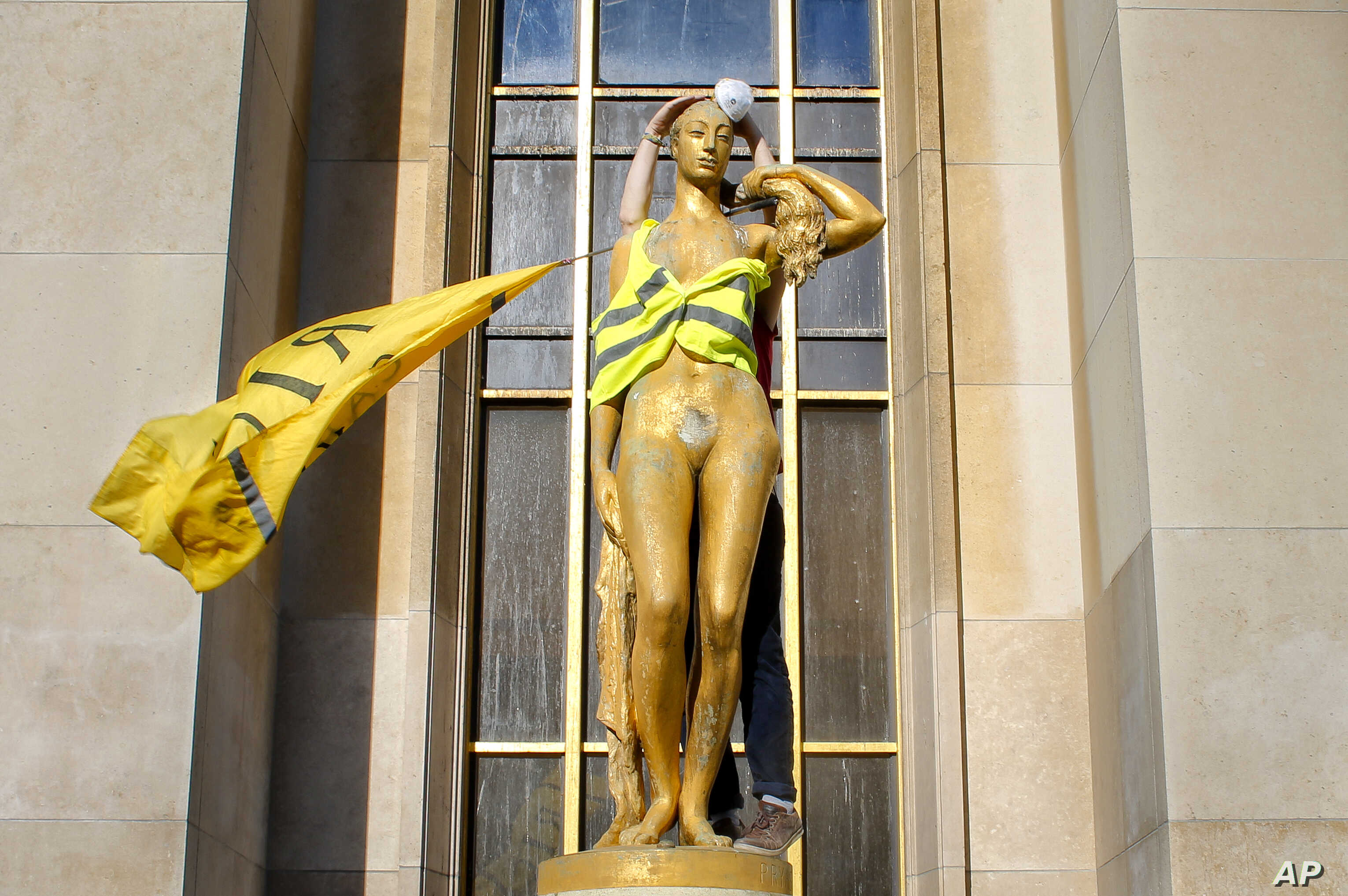 """A demonstrator places a mask and a yellow vest on a statue titled """"Le Matin,"""" or """"The Morning,"""" as French """"yellow vest"""" protesters rally in support of a fellow activist who was injured in a recent confrontation with police, March 30, 2019, in Trocade..."""
