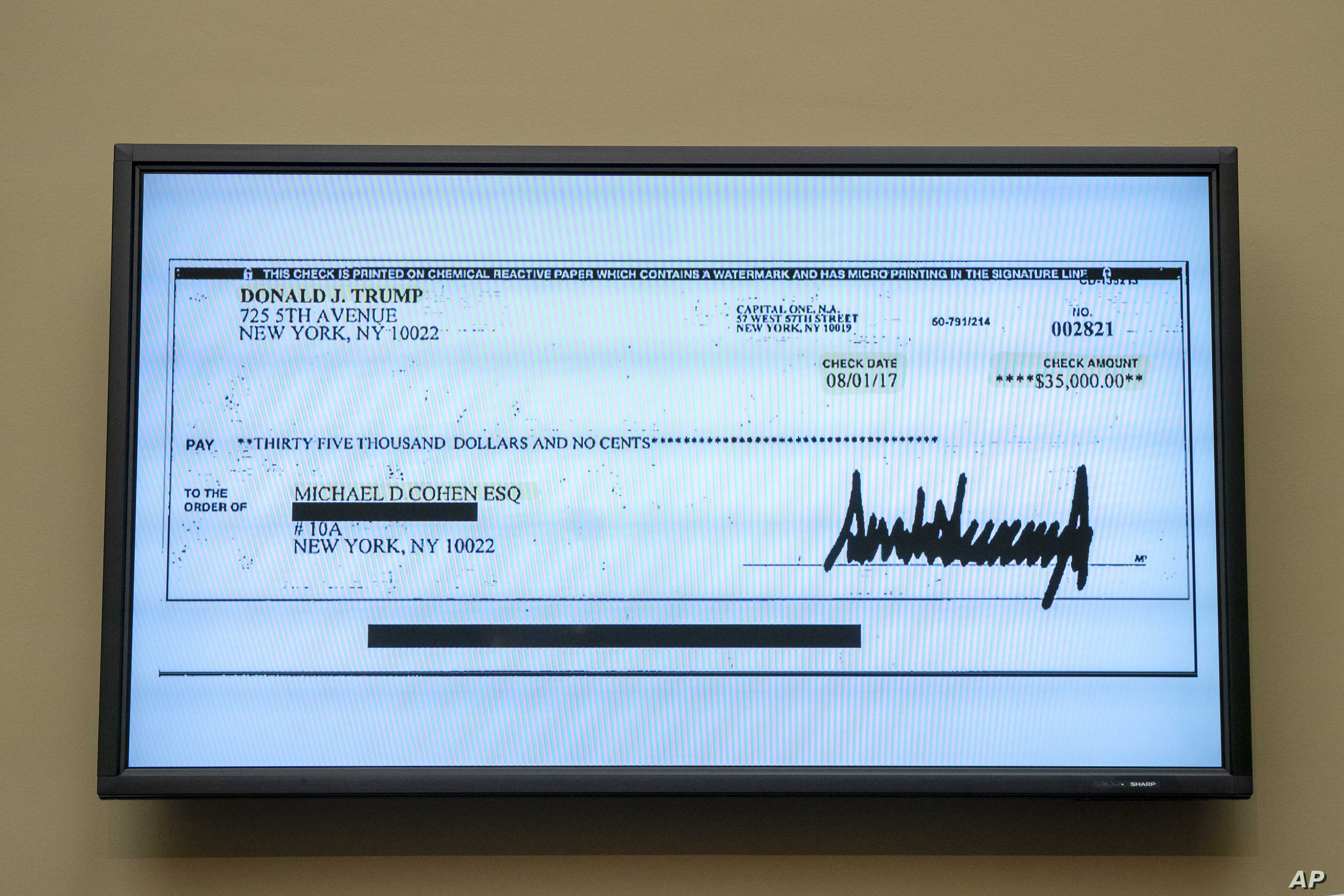 A copy of a check from Donald Trump to Michael Cohen, his former personal lawyer, is displayed as he testifies before the House Oversight and Reform Committee on Capitol Hill in Washington, Feb. 27, 2019.