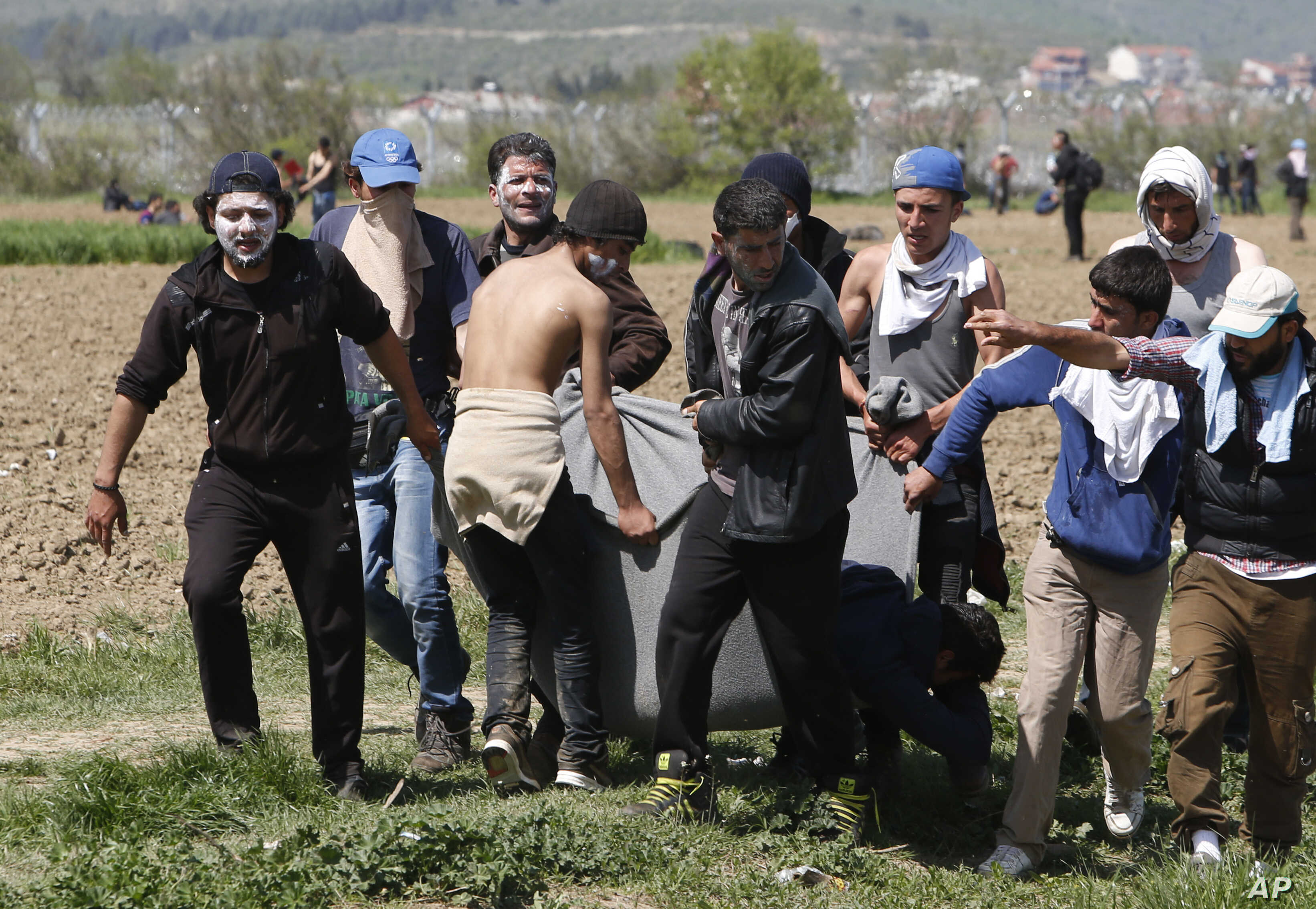 Migrants carry a wounded man in a blanket during a protest at the northern Greek border point of Idomeni, Greece, April 10, 2016.