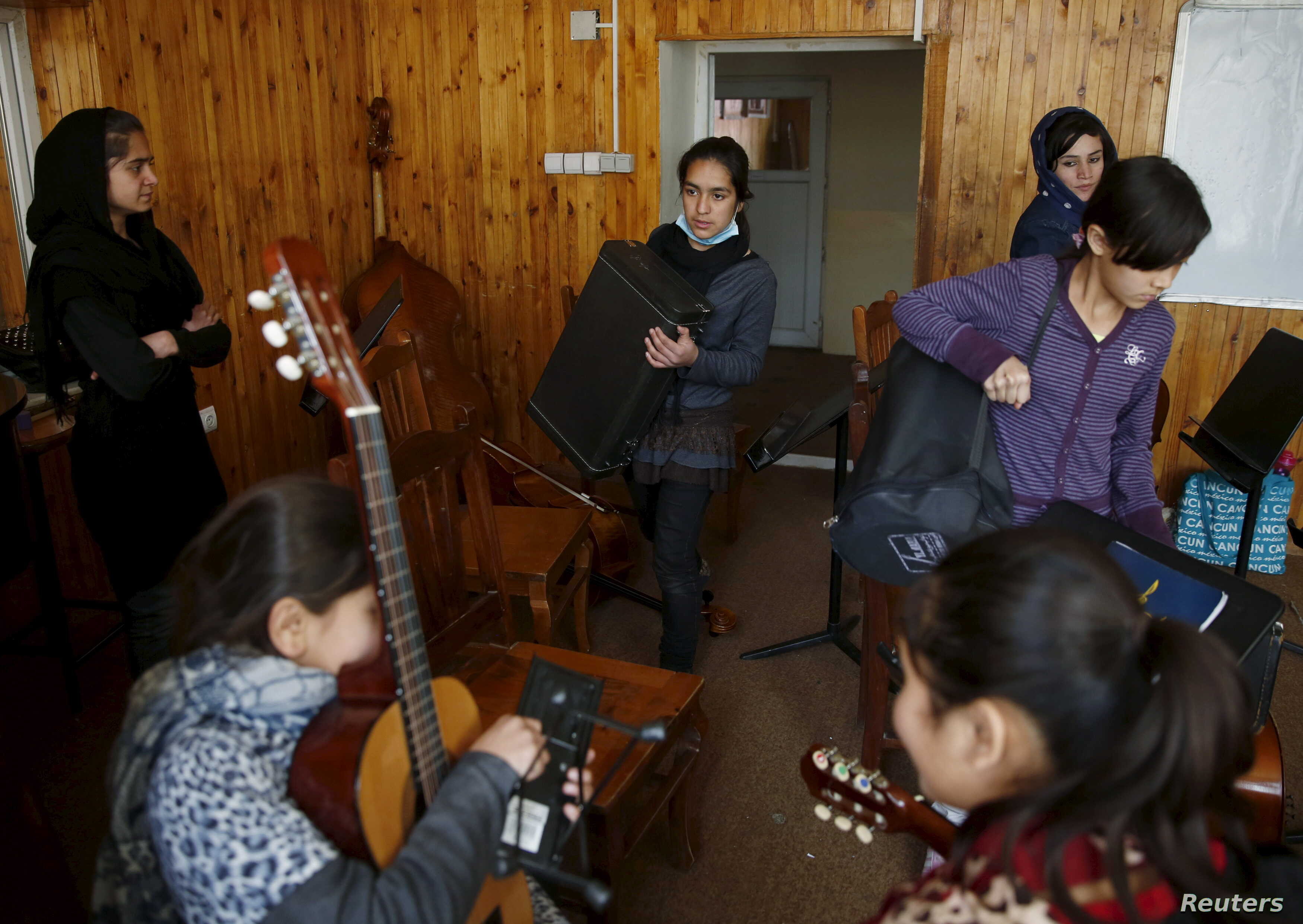 FILE - Members of the Zohra orchestra, an ensemble of 35 women, bring instruments to a class before a rehearsal at Afghanistan's National Institute of Music, in Kabul, Afghanistan, April 4, 2016.