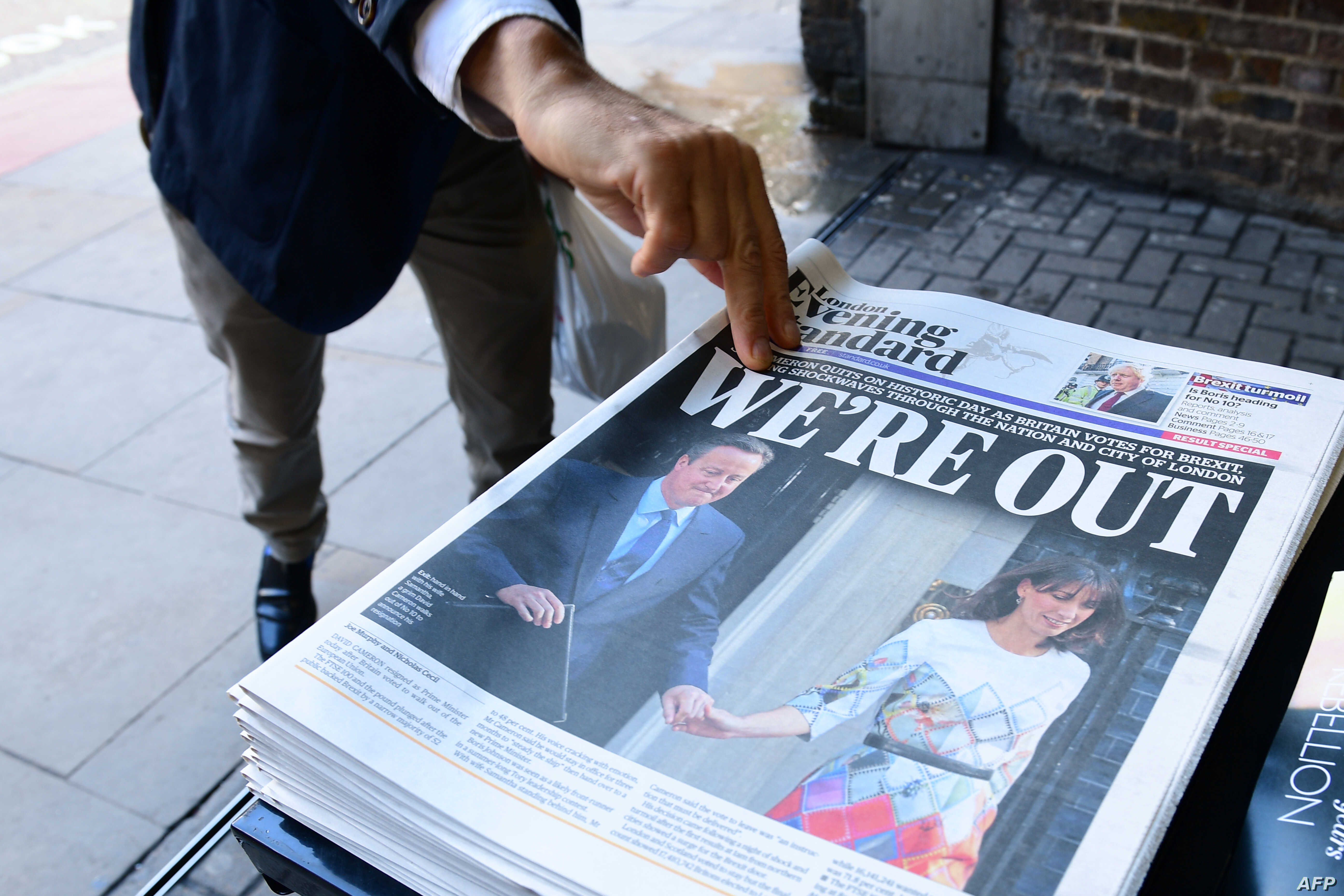A man takes a copy of the London Evening Standard with the front page reporting the resignation of British Prime Minister David Cameron and the vote to leave the EU in a referendum on June 24, 2016.