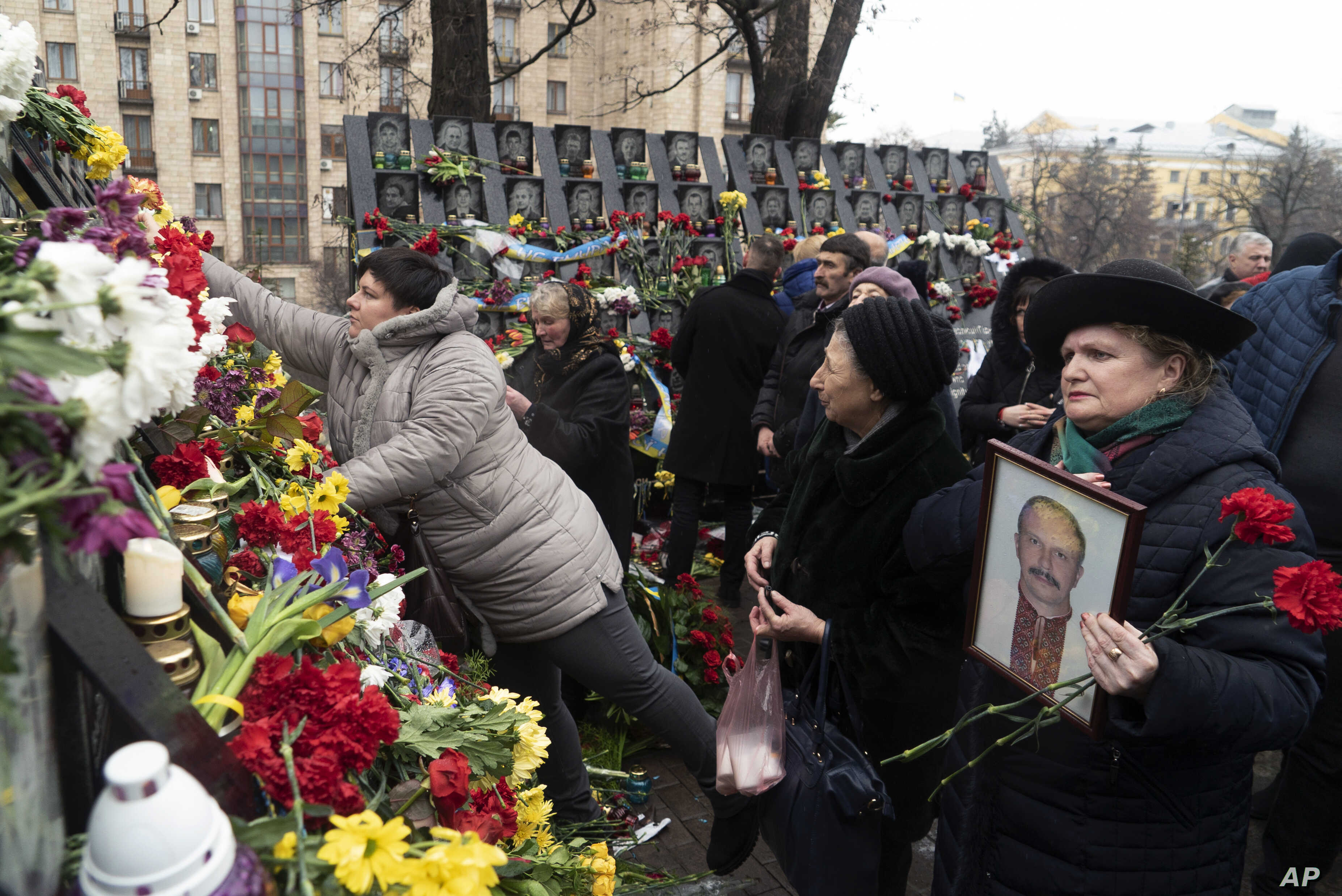 People place flowers to pay their respect at a memorial dedicated to people who died in clashes in early 2014 with security forces in central Kyiv during mass protests that ousted pro-Russia president Viktor Yanukovych, at Independent Square (Maidan)...