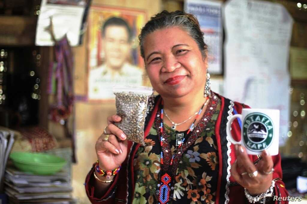 Local chieftain Baby Jerlina Owok poses for a photo with coffee beans grown by her community in Mindanao, the Philippines, March 26, 2018.