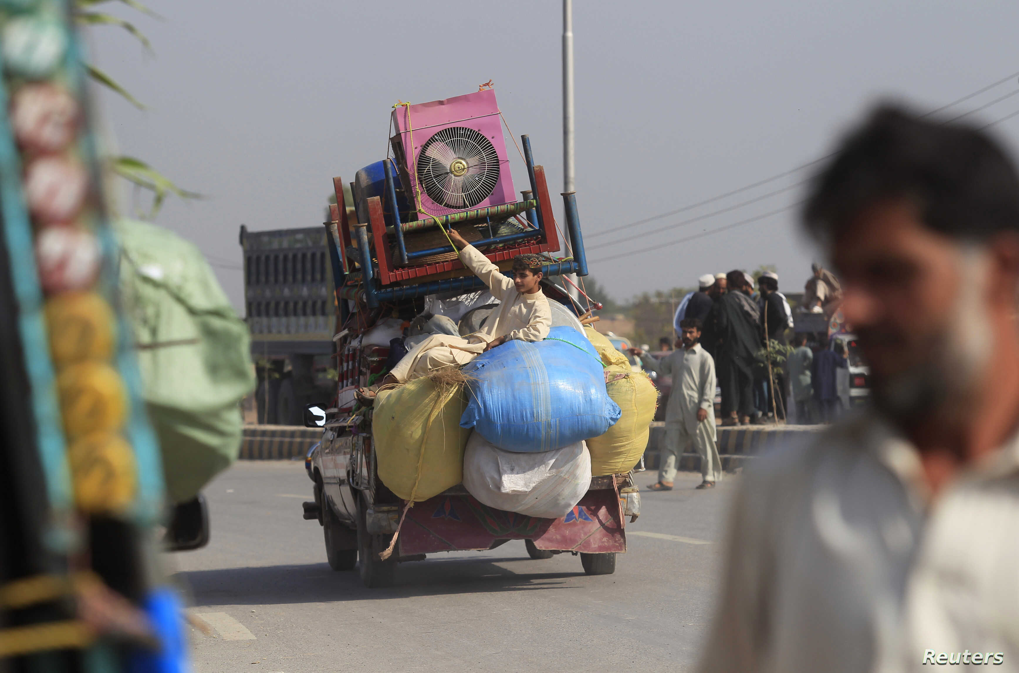 FILE - A man fleeing a military offensive against militants in the Khyber Agency, travels on a vehicle laden with his family's belongings on the outskirts of Peshawar in Pakistan's Khyber-Pakhtunkhwa province Oct. 30, 2014.