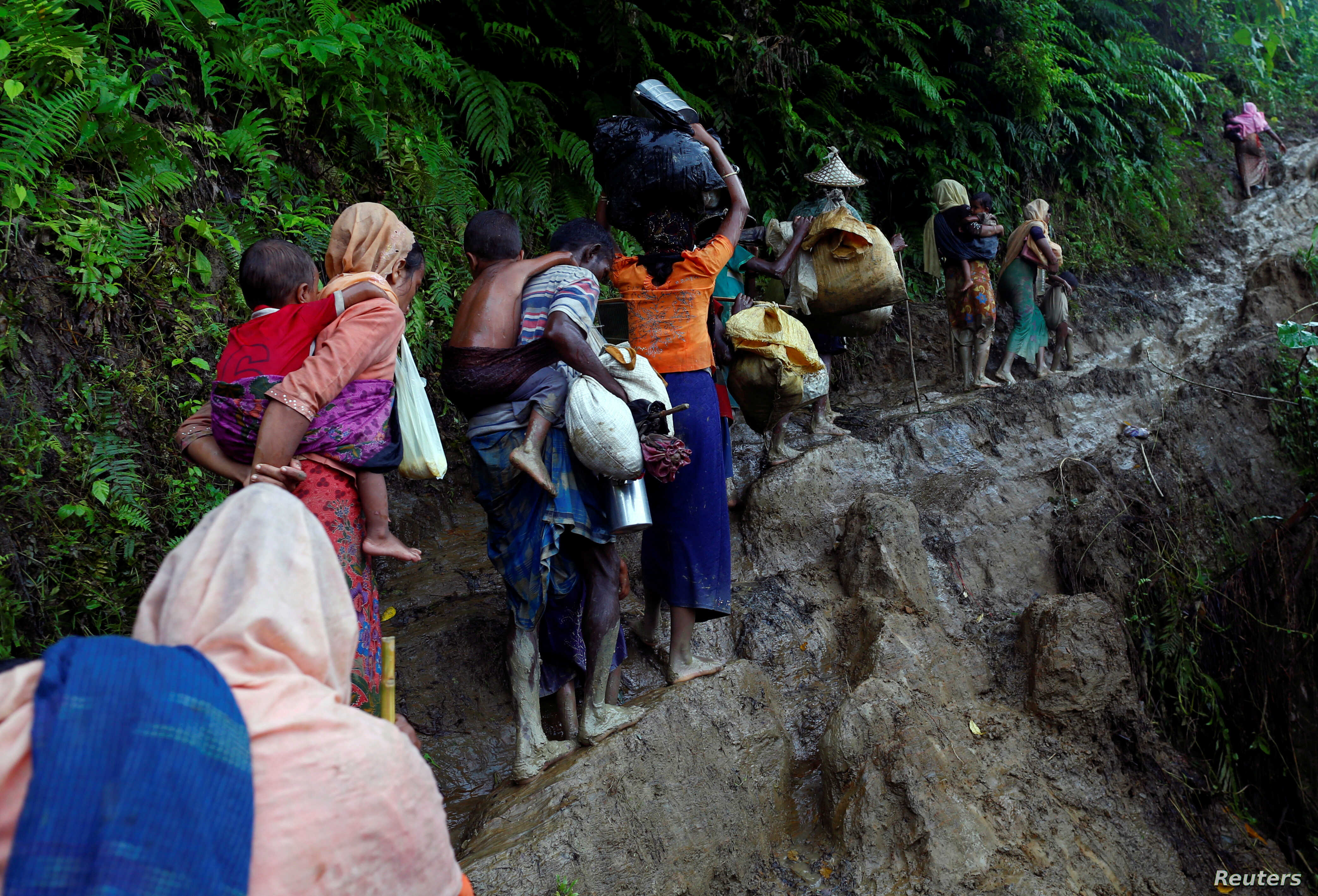 Rohingya refugees climb up a hill after crossing the Bangladesh-Myanmar border in Cox's Bazar, Bangladesh, Sept. 8, 2017.
