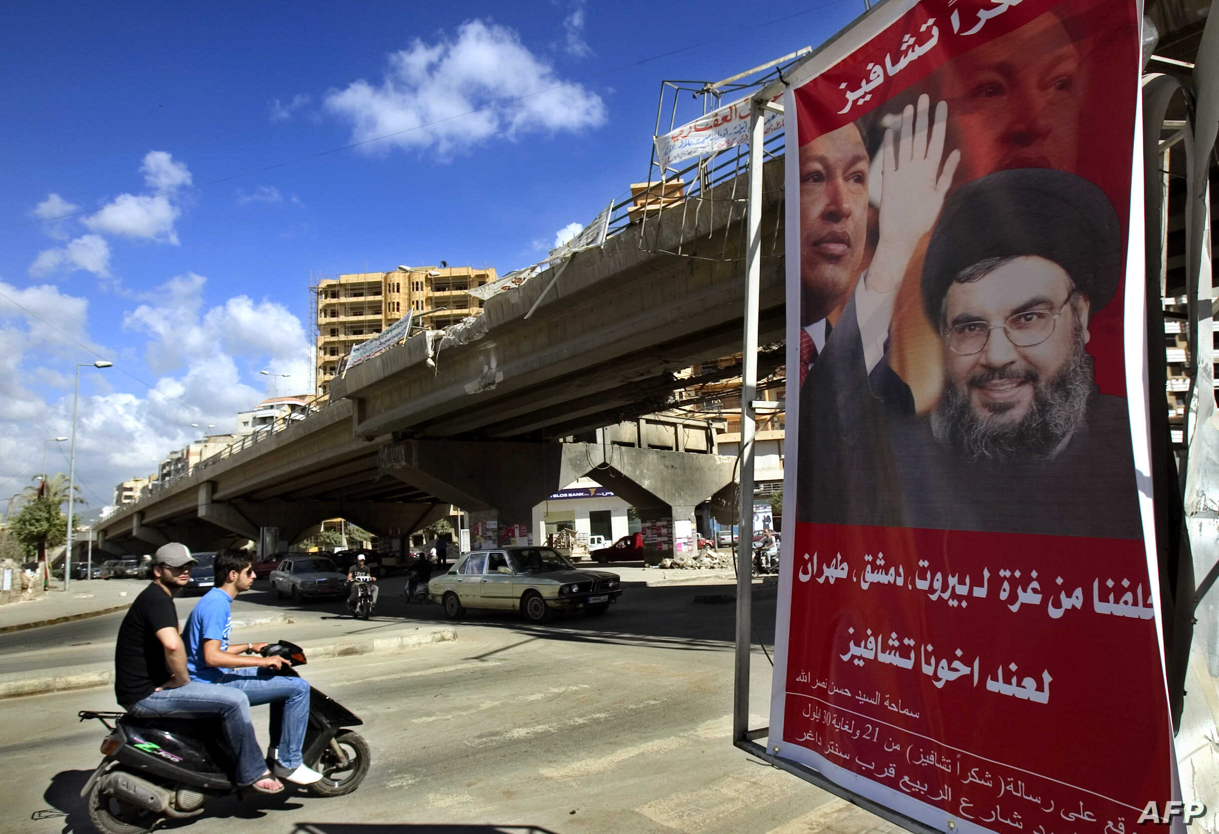 "FILE - A poster shows Hassan Nasrallah, the Secretary-General of Hezbollah, and Venezuela's President Hugo Chavez, along with a slogan that reads ""Gracias Chavez"" is seen hanging from a destroyed bridge at the entrance of southern suburb of Beirut, S..."