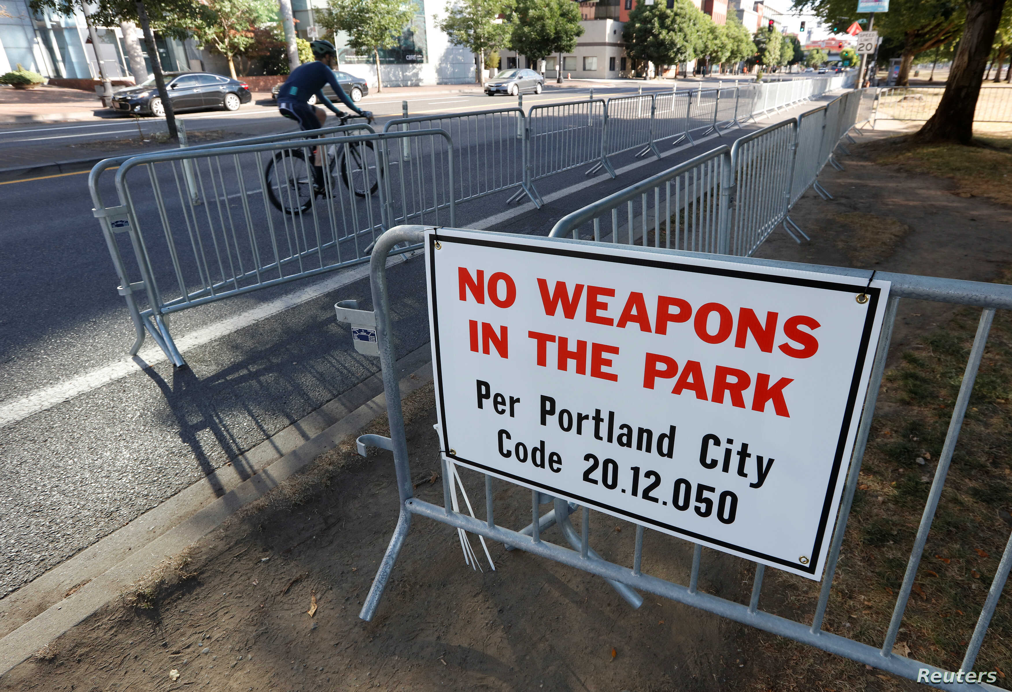 """A """"No Weapons"""" sign is seen at a park where the right-wing Patriot Prayer group planned to rally in Portland, Ore., Aug. 4, 2018."""