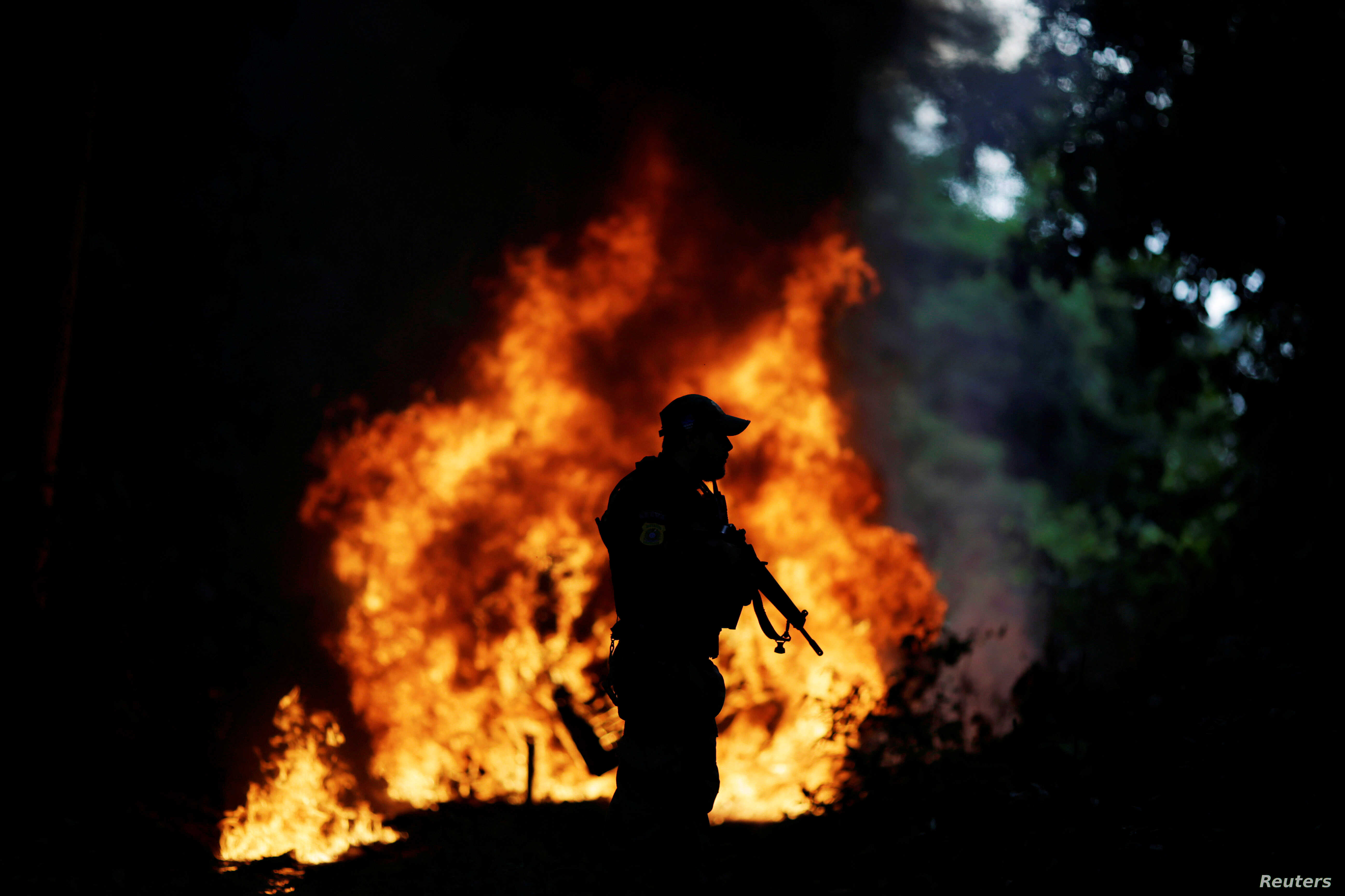 Trucks loaded with tree trunks are burned by agents of the Brazilian Institute for the Environment and Renewable Natural Resources, or Ibama, during an operation to combat illegal mining and logging, in the municipality of Novo Progresso, Para State,...