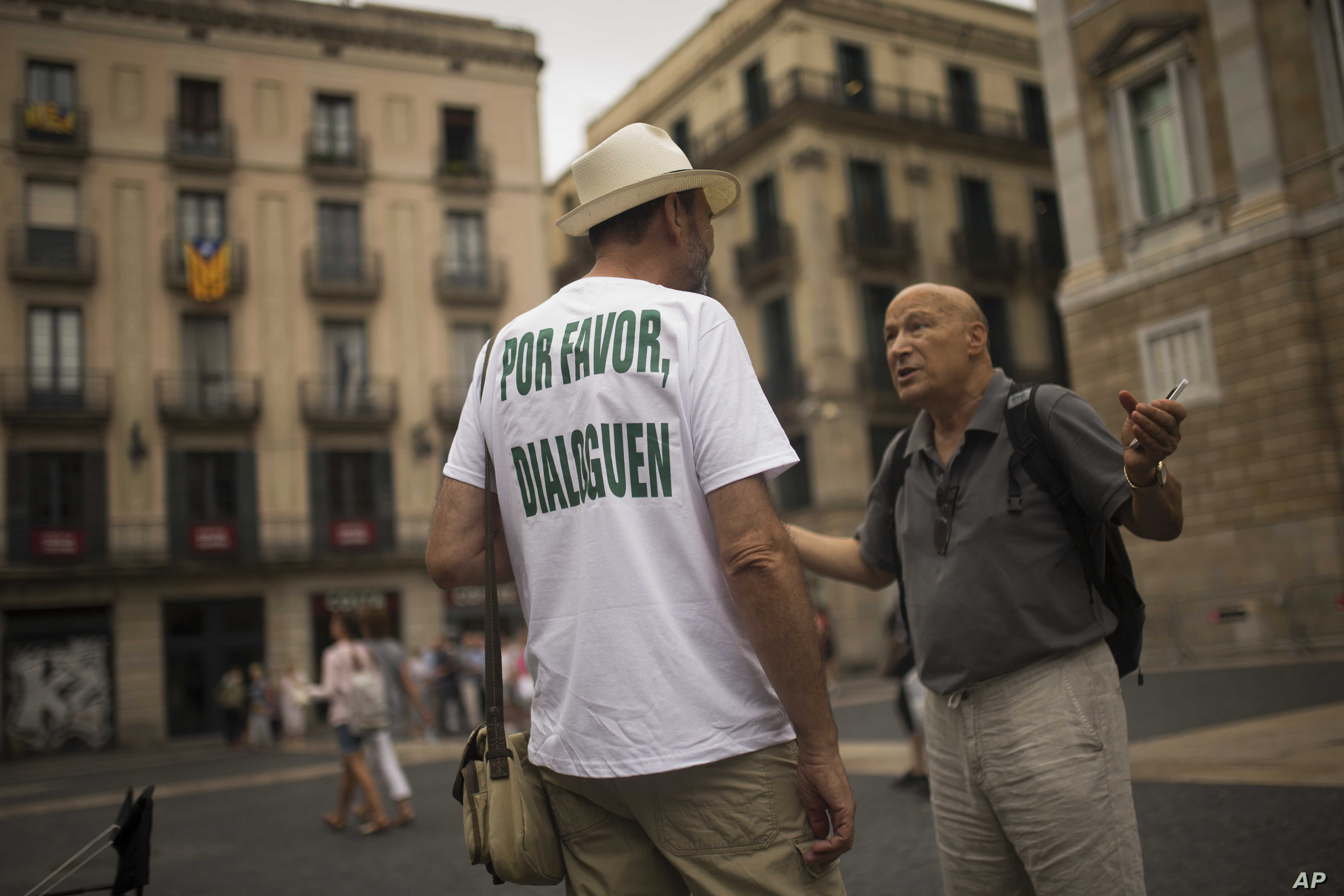 "A man, wearing a t-shirt reading in Spanish: ""Please, talk"" chats with a passer-by about the current political situation in Catalonia, in Barcelona, Oct. 6, 2017."