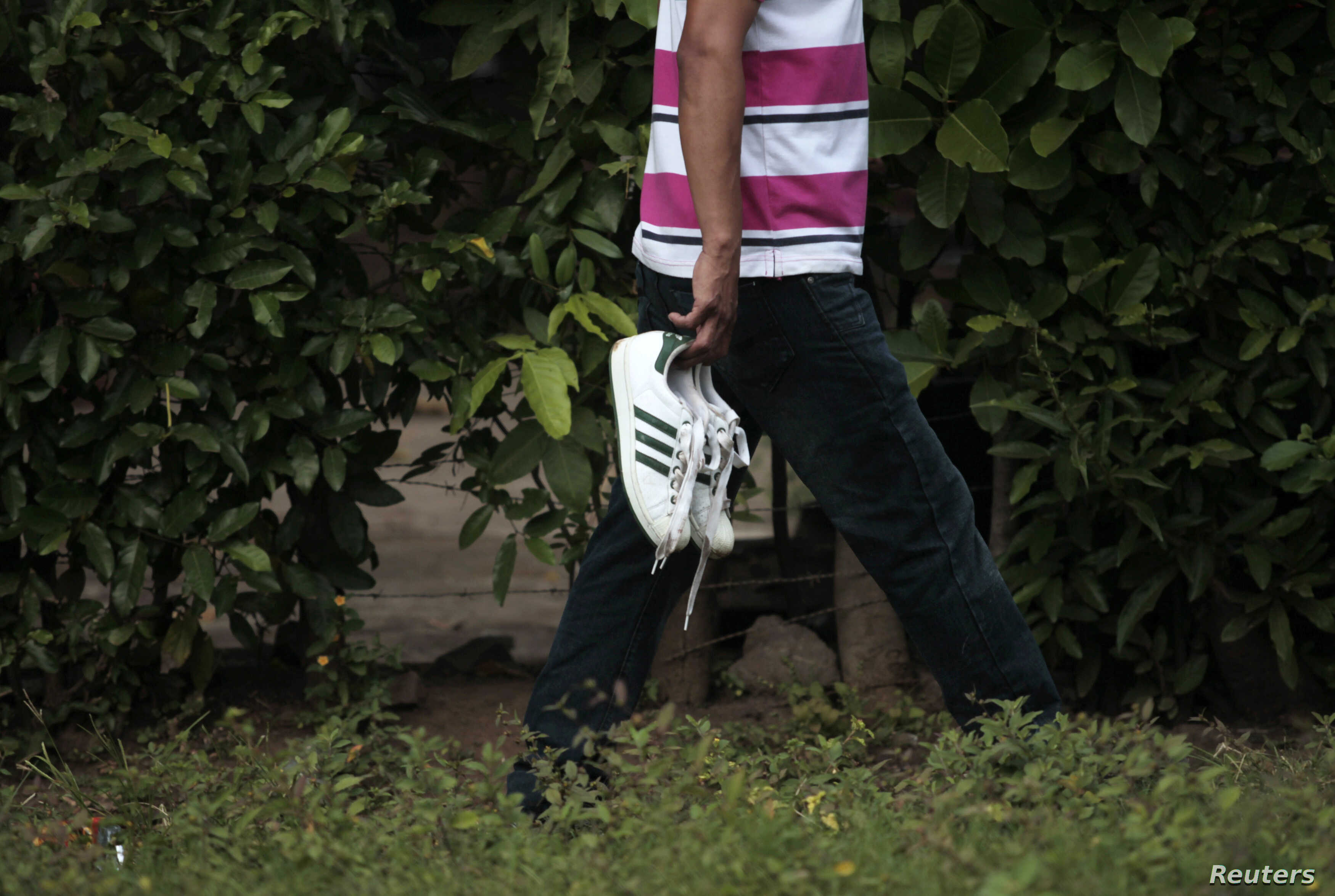 A man carries the shoes of his son after identifying him as among the seven men who were shot during a middle school graduation party in the town of Acajutla, El Salvador, Nov. 25, 2014.