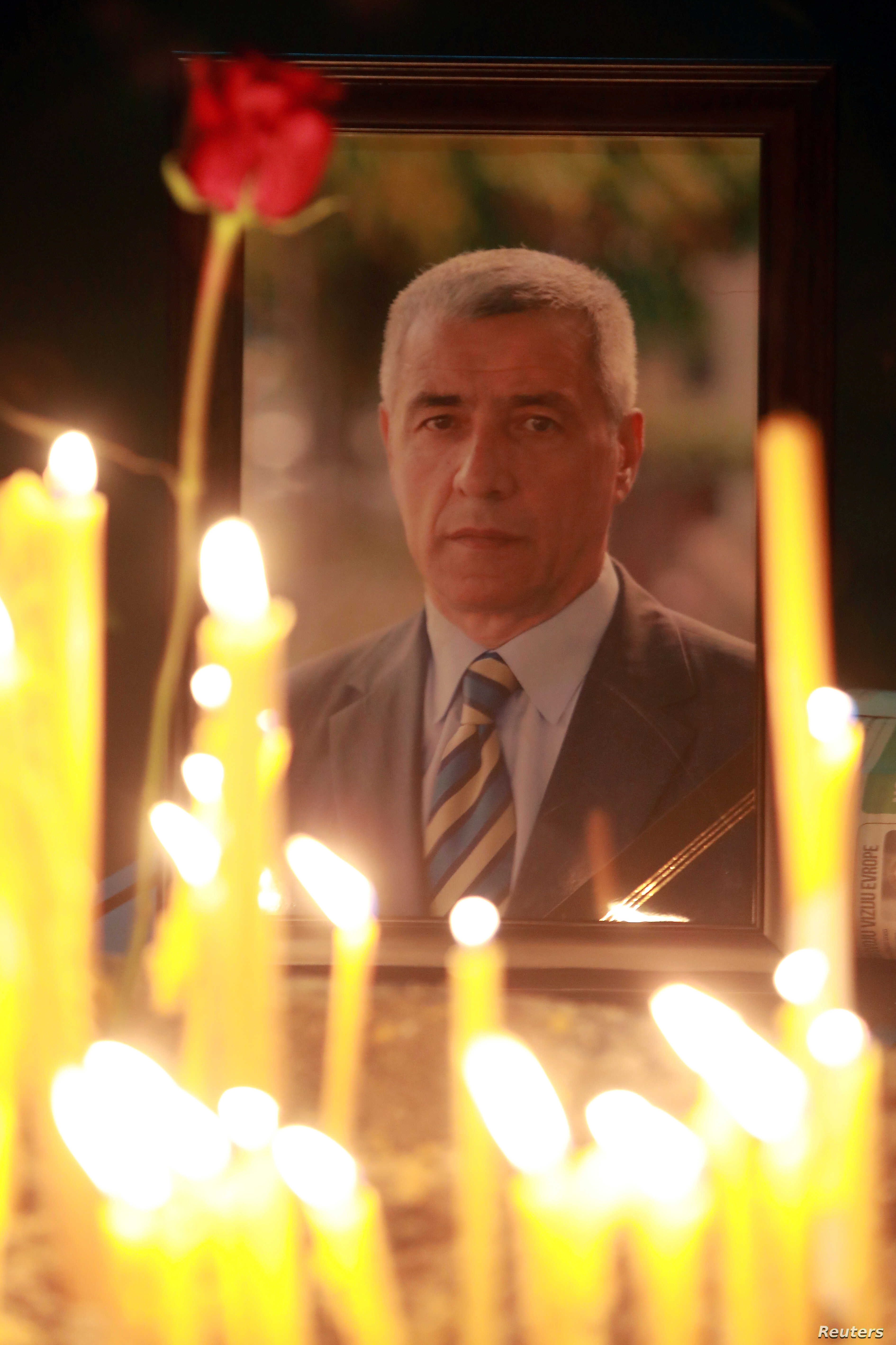 FILE - A portrait of Oliver Ivanovic is seen during a memorial service for the Kosovo Serb leader in Mitrovica, Kosovo, Jan. 16, 2018.