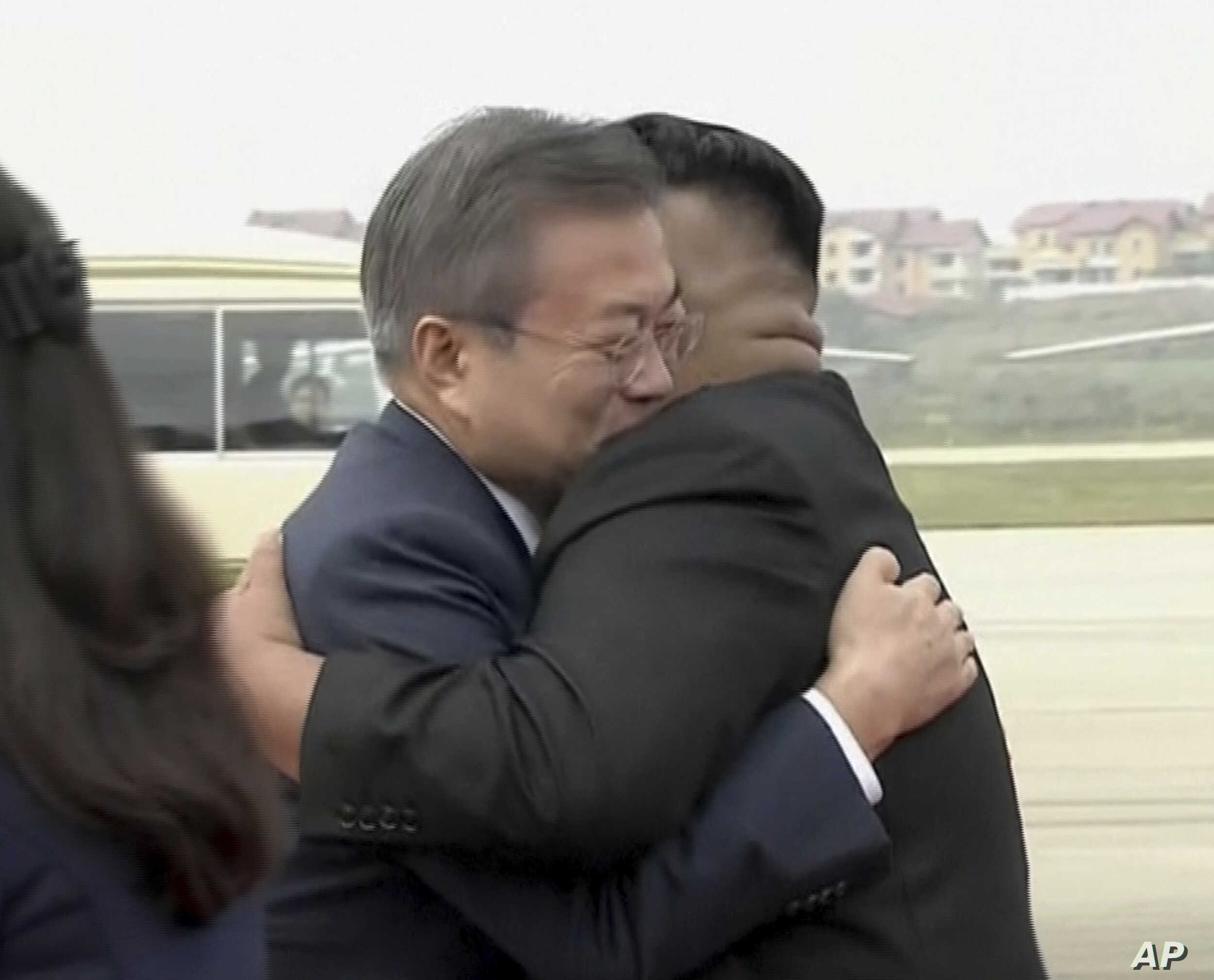 South Korean President Moon Jae-in, left, hugs North Korean leader Kim Jong Un upon arrival in Pyongyang, North Korea, Tuesday, Sept. 18, 2018.