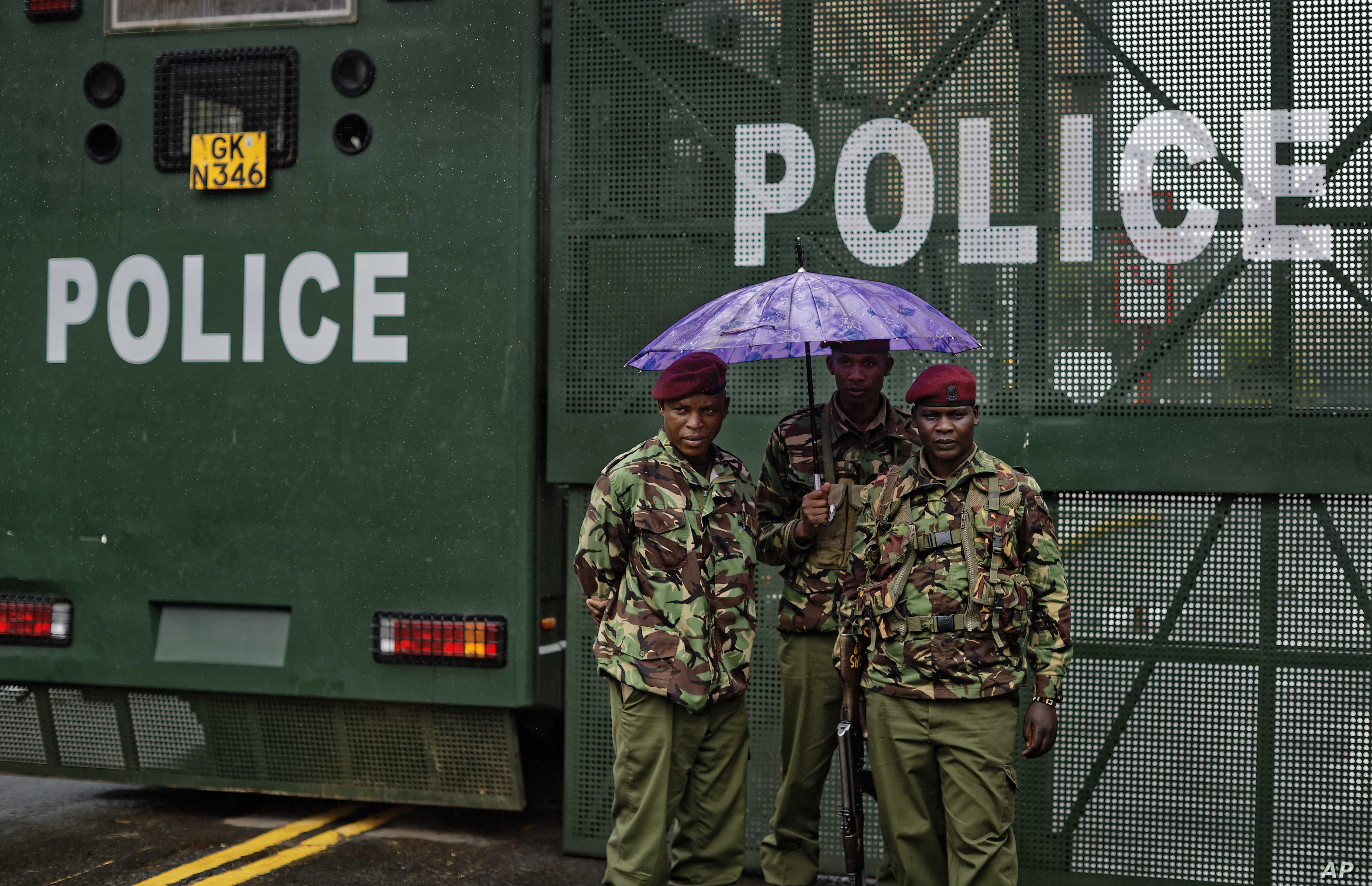 Kenyan police officers stand in the rain by a barrier blocking off vehicle and pedestrian access, amid tight security outside the Supreme Court in Nairobi, Kenya, Nov. 14, 2017.