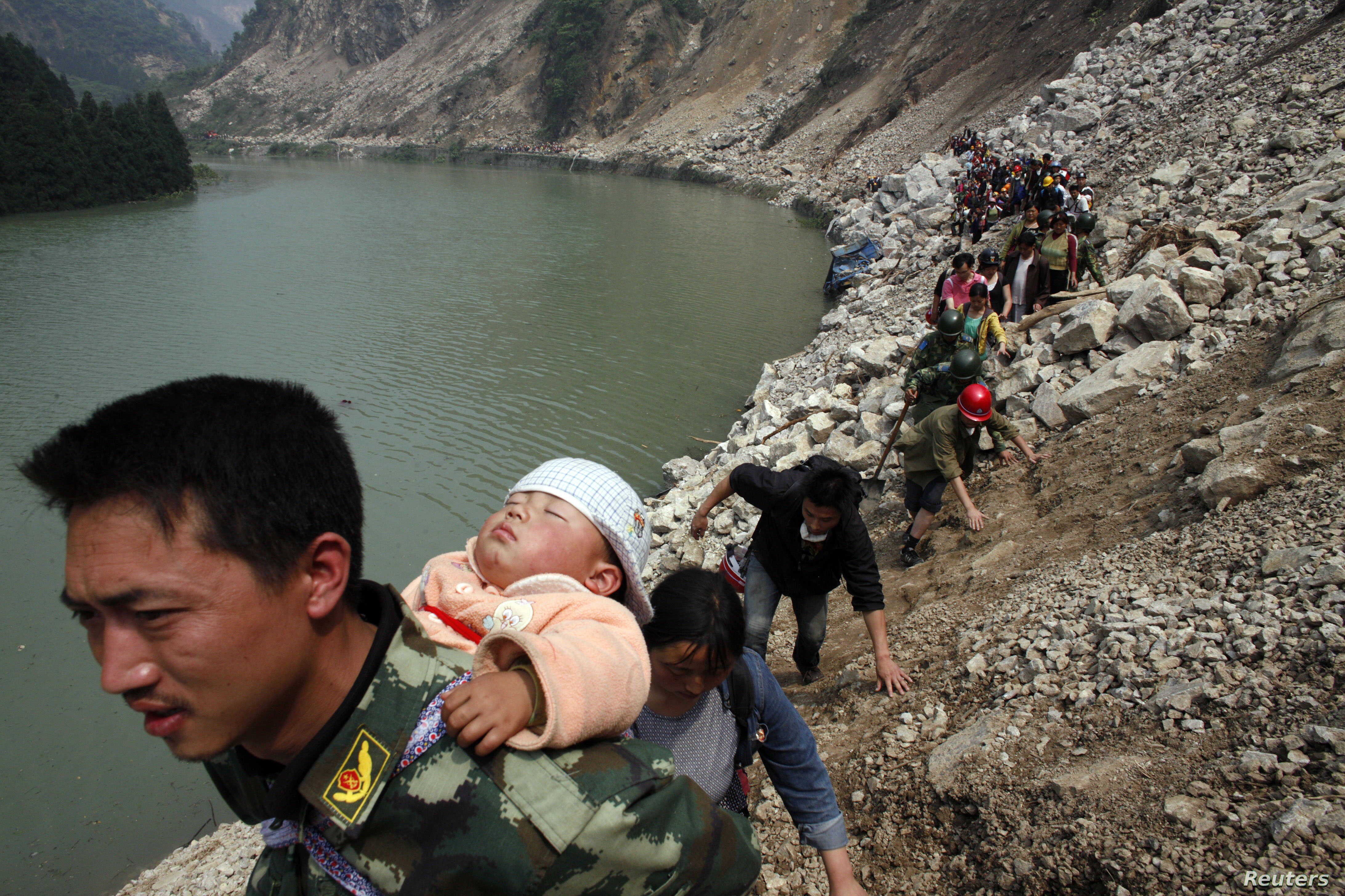 FILE - Survivor carries baby on his back as he and some 1,000 other survivors make a  9-hour walk from the village of Qingping to Hanwang, after earthquake, Sichuan Province, China, May 16, 2008.