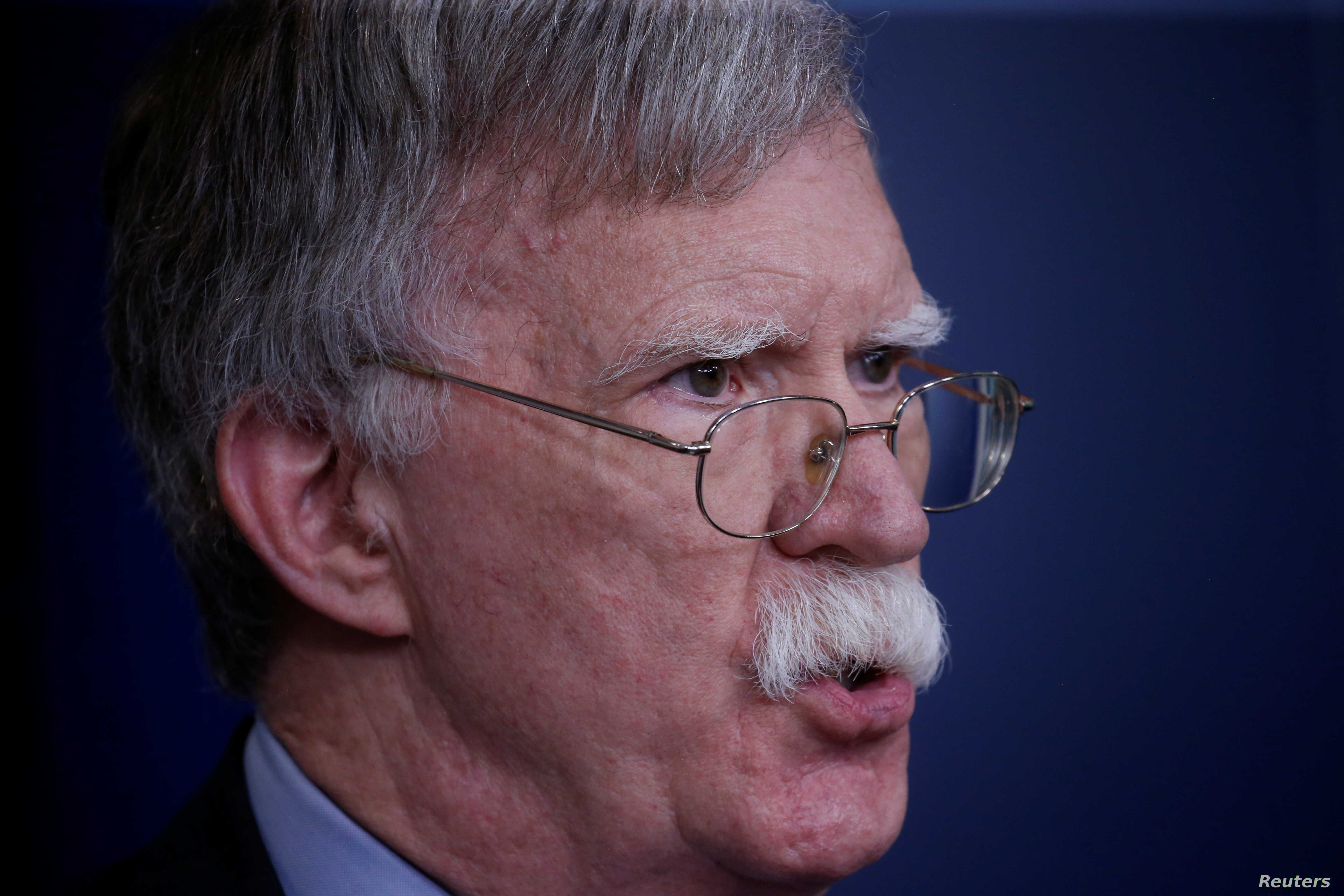 """FILE - U.S. national security adviser John Bolton answers questions from reporters after announcing that the U.S. will withdraw from the Vienna protocol and the 1955 """"Treaty of Amity"""" with Iran, during a news conference in the White House briefing ro..."""