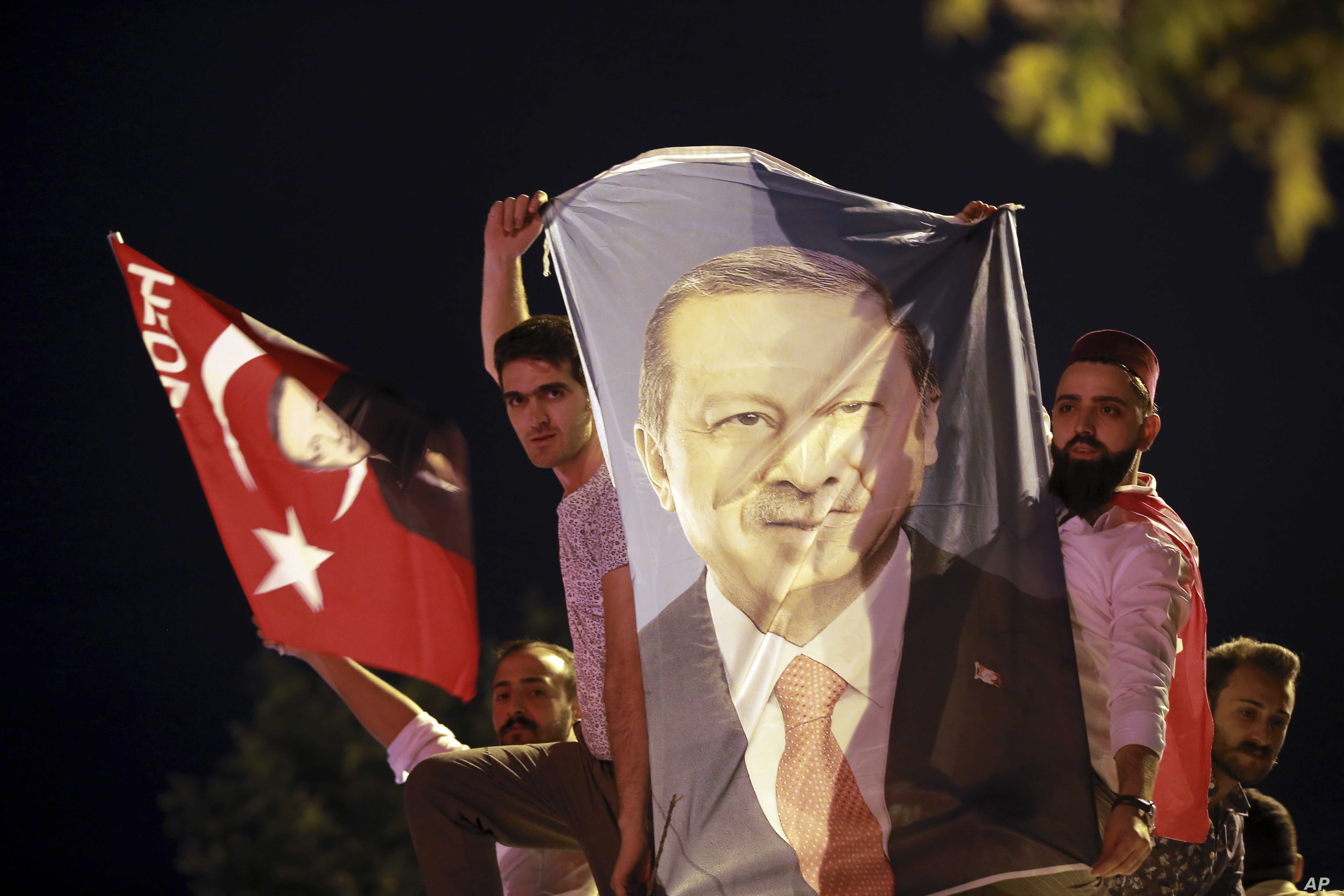Men, holding a banner with a picture of Turkey's President Recep Tayyip Erdogan, celebrate outside his Justice and Development Party, or AKP, headquarters in Istanbul, June 24, 2018.