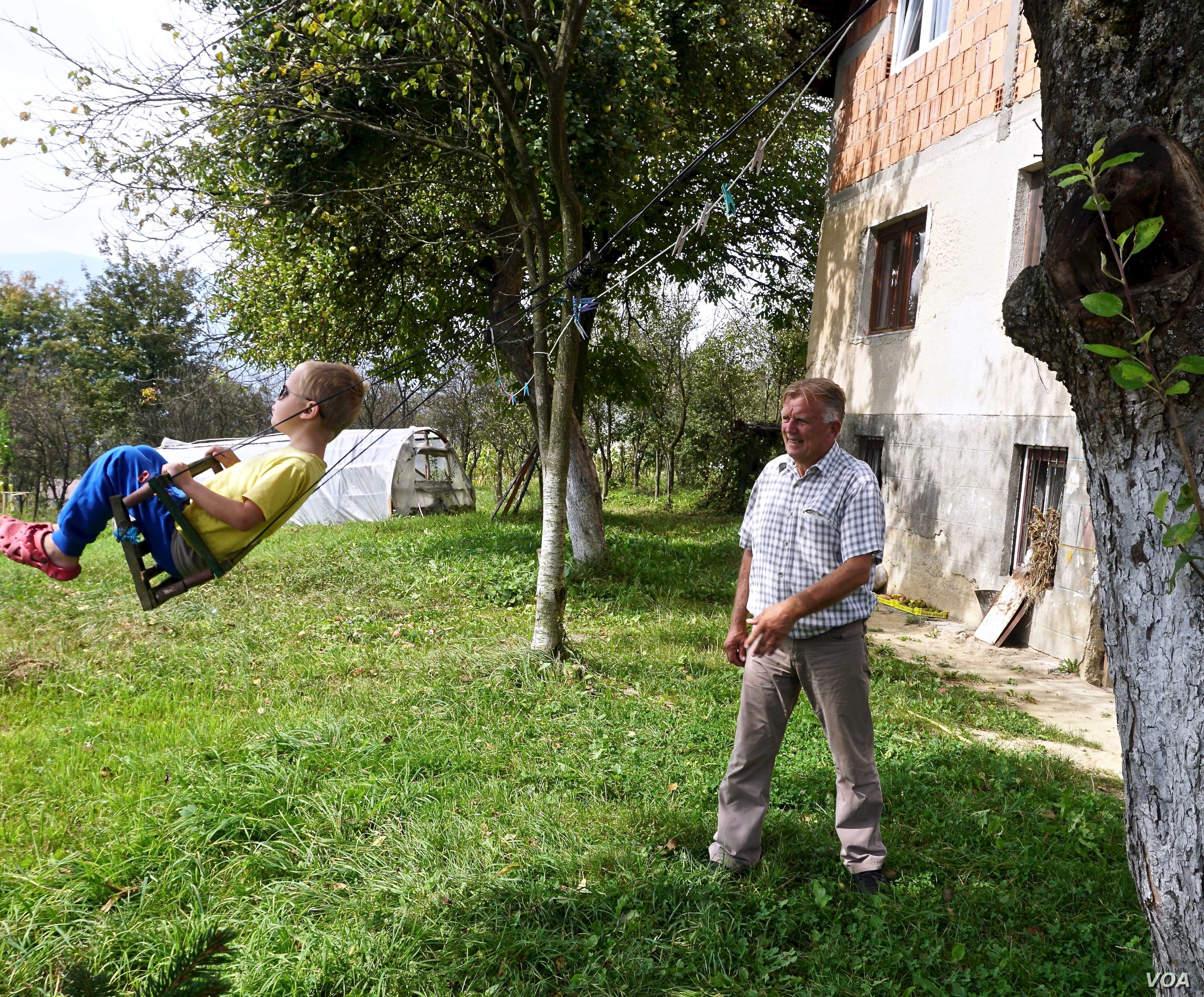 Huso Ahmić, now 72 years-old, plays with a grandson in the garden of his family home, which was rebuilt after it was razed in the 1993 attack. His parents died in the blaze.