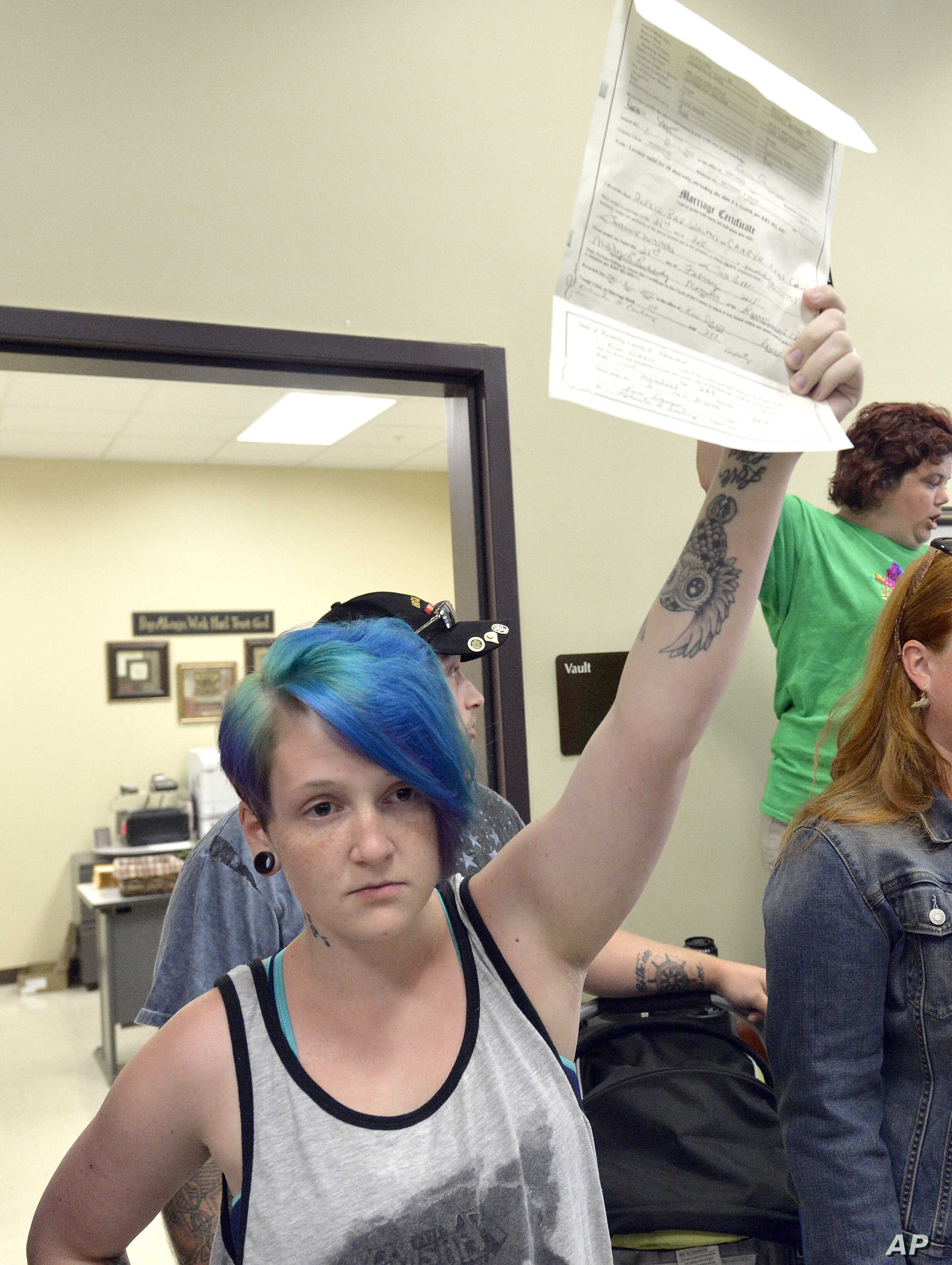 Lexie Colon holds up her marriage certificate at the Rowan County Courthouse in Morehead, Ky., Sept. 1, 2015. Signed by clerk Kim Davis, it certifies her marriage to Camryn Colon, a transgender male.