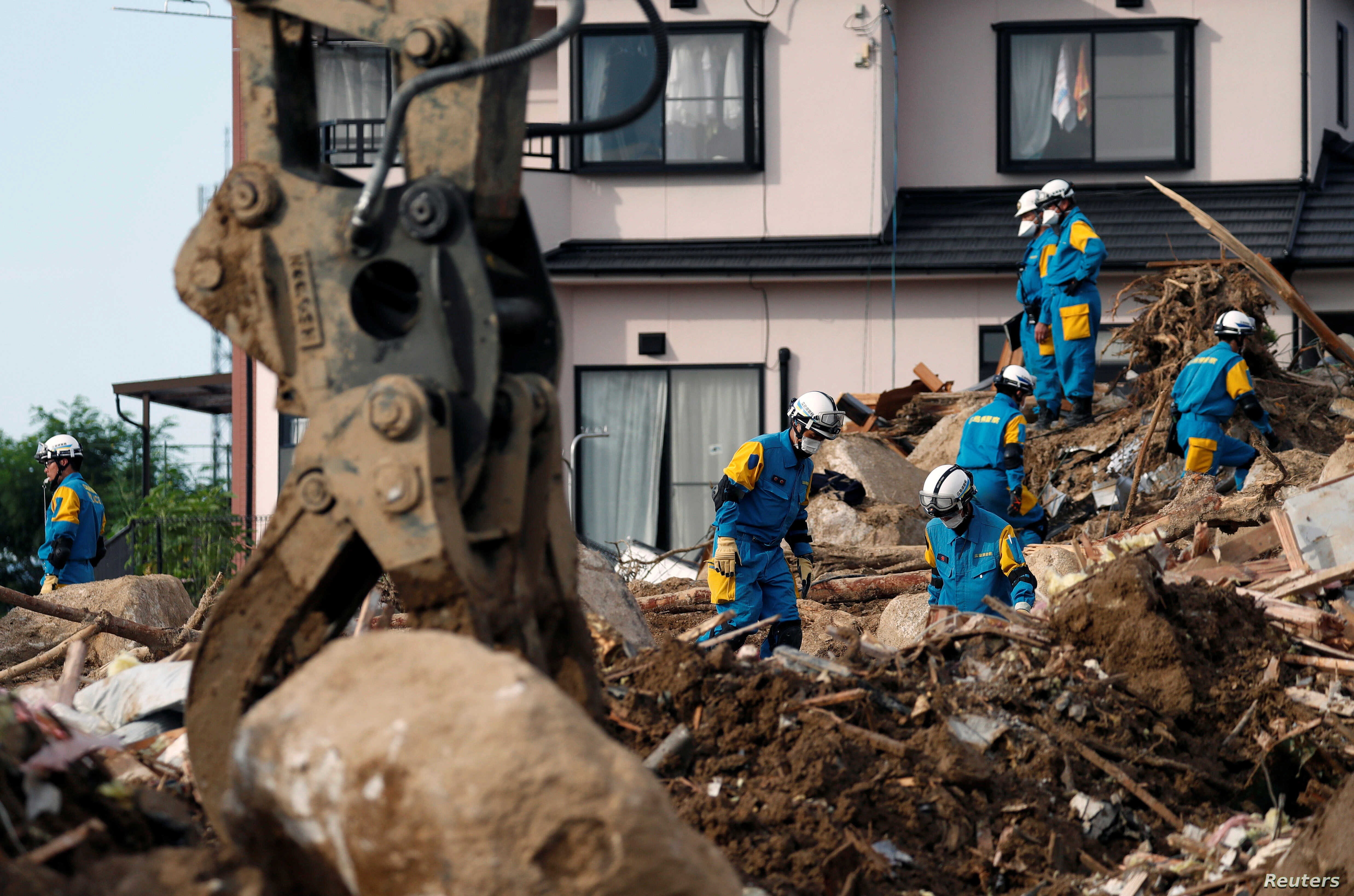 Rescue workers search for missing people at a landslide site caused by heavy rain in Kumano Town, Hiroshima Prefecture, Japan, July 11, 2018.