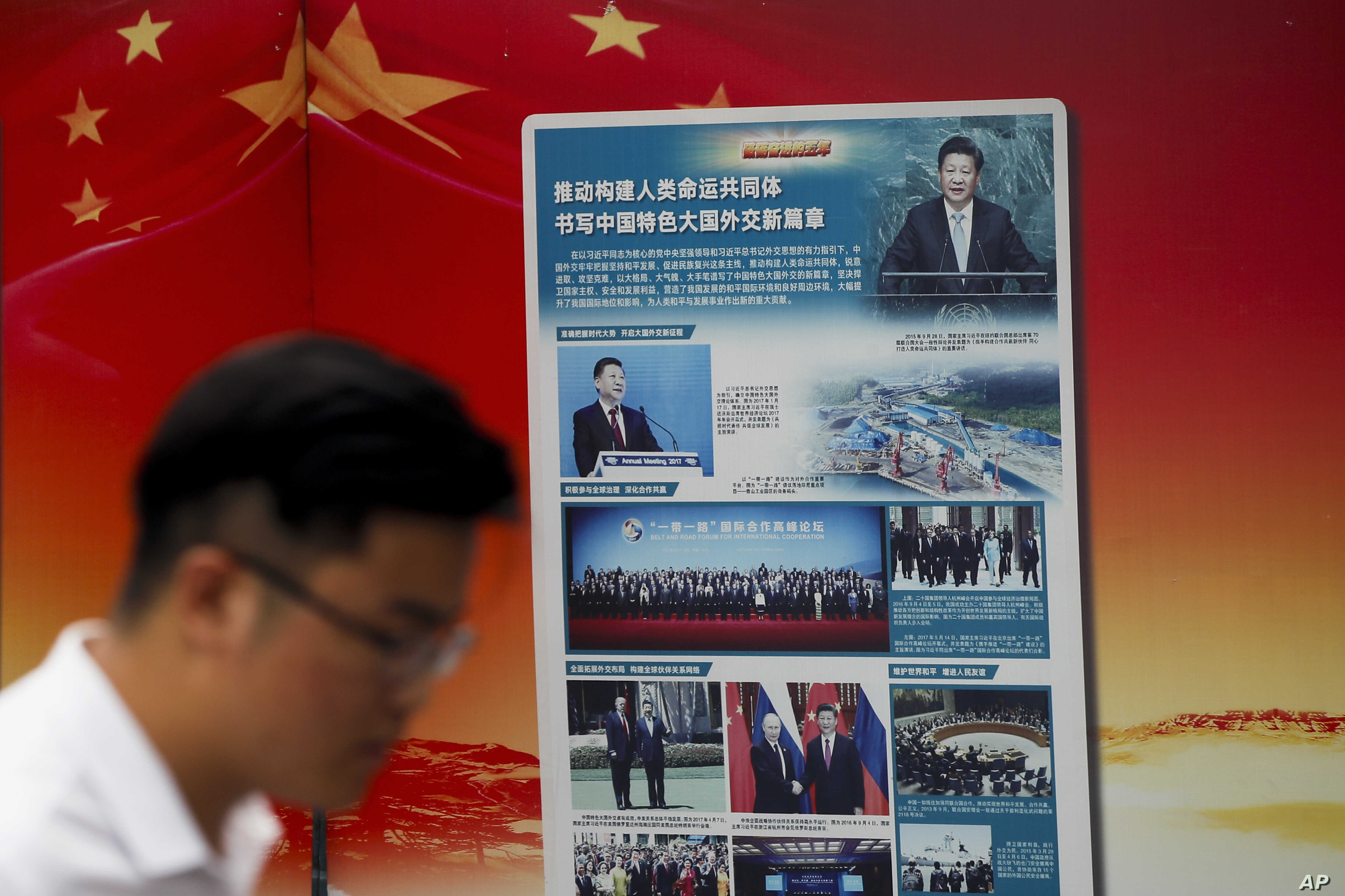 """A man walks by a government propaganda billboard promoting Chinese President Xi Jinping's signature """"One Belt One Road"""" outside a subway station in Beijing, Aug. 28, 2018."""