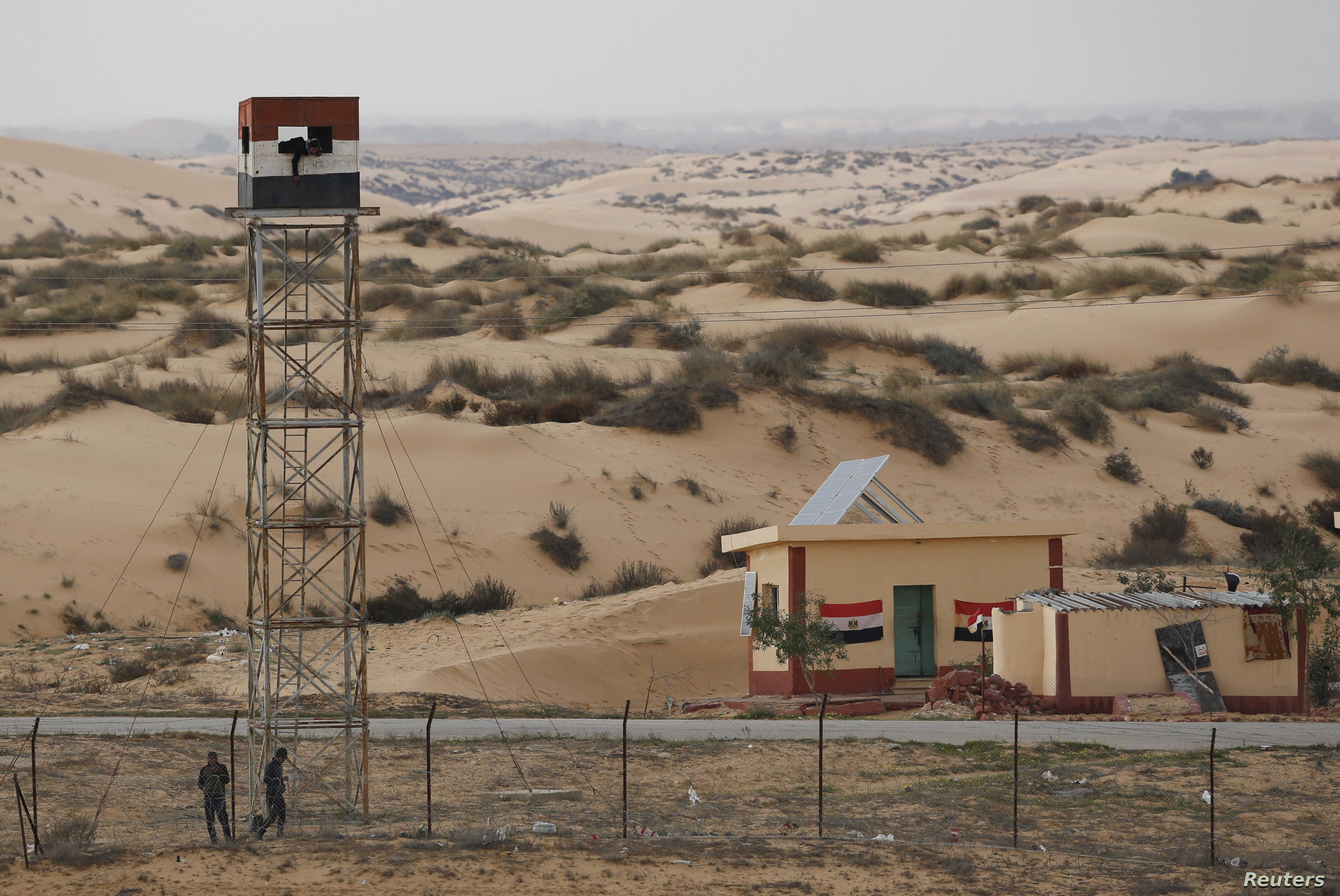 An Egyptian policeman gestures from an observation tower is seen from the Israeli side of the border with Egypt's Sinai peninsula, in Israel's Negev Desert February 10, 2016. REUTERS/Amir Cohen
