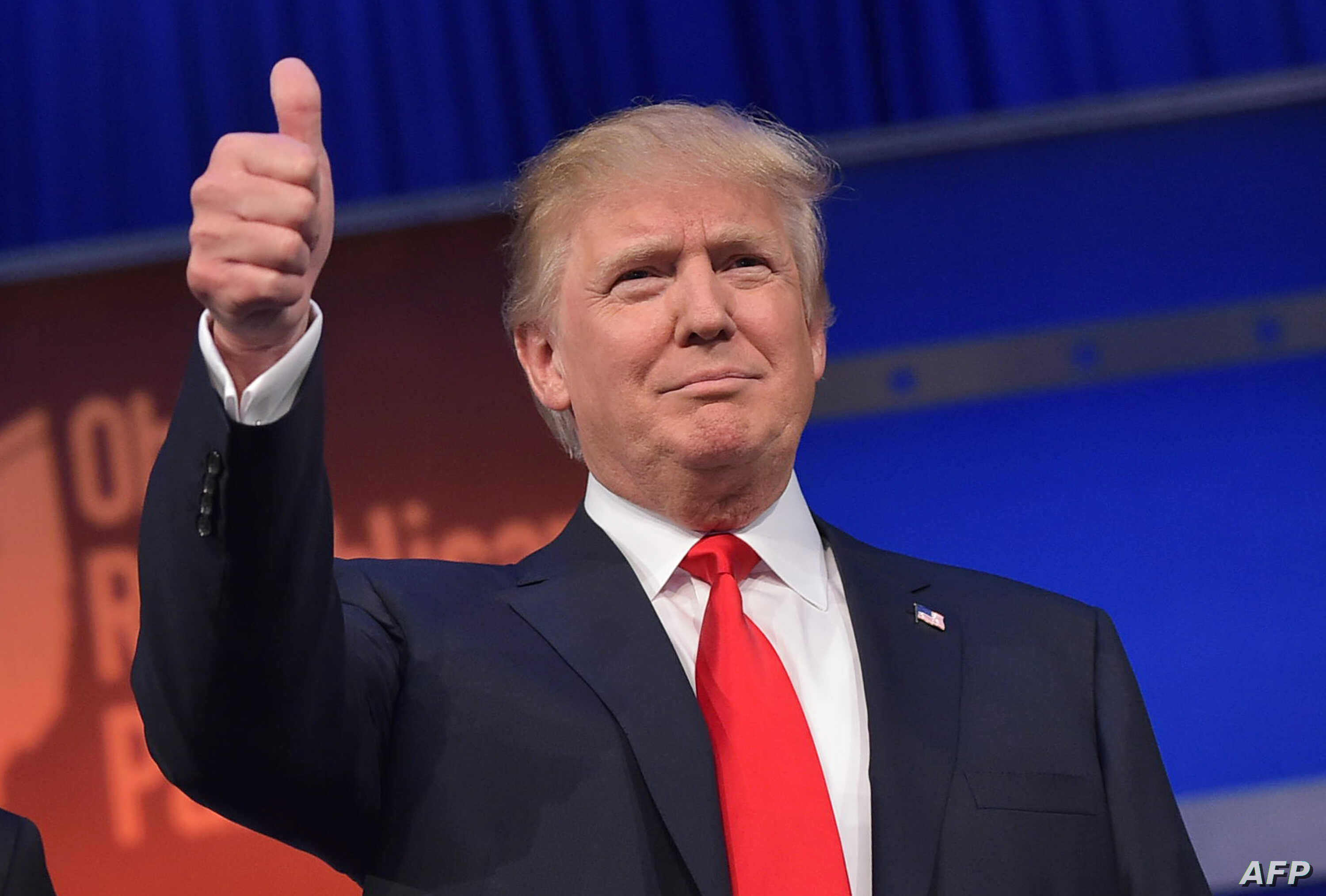 Real estate tycoon Donald Trump flashes the thumbs-up as he arrives on stage for the start of the prime time Republican presidential debate on Aug. 6, 2015 at the Quicken Loans Arena in Cleveland, Ohio.