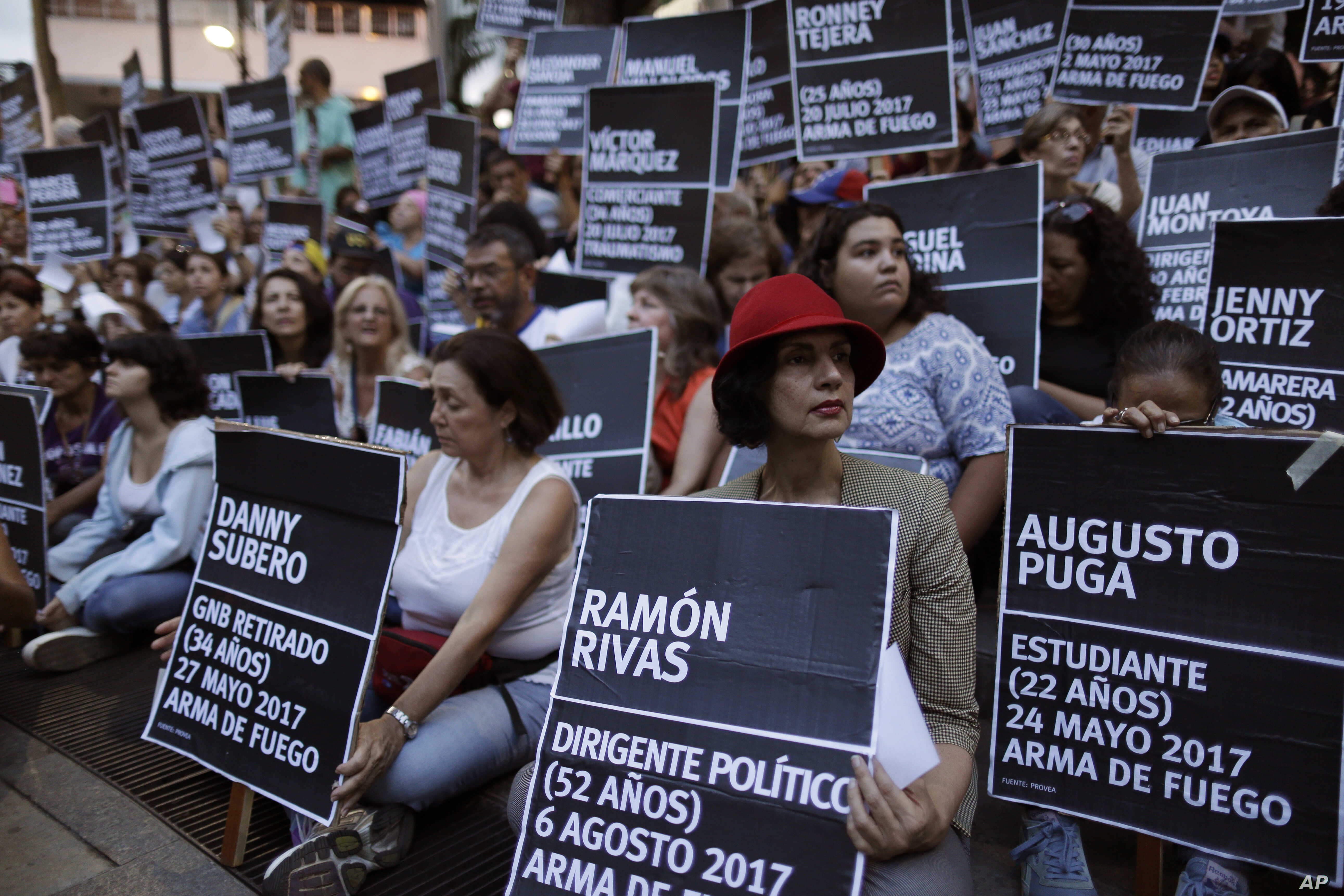 FILE - Anti-government demonstrators hold the names of people killed during months of deadly protests against Venezuelan President Nicolas Maduro, at a park in Caracas, Venezuela, Aug. 30, 2017.