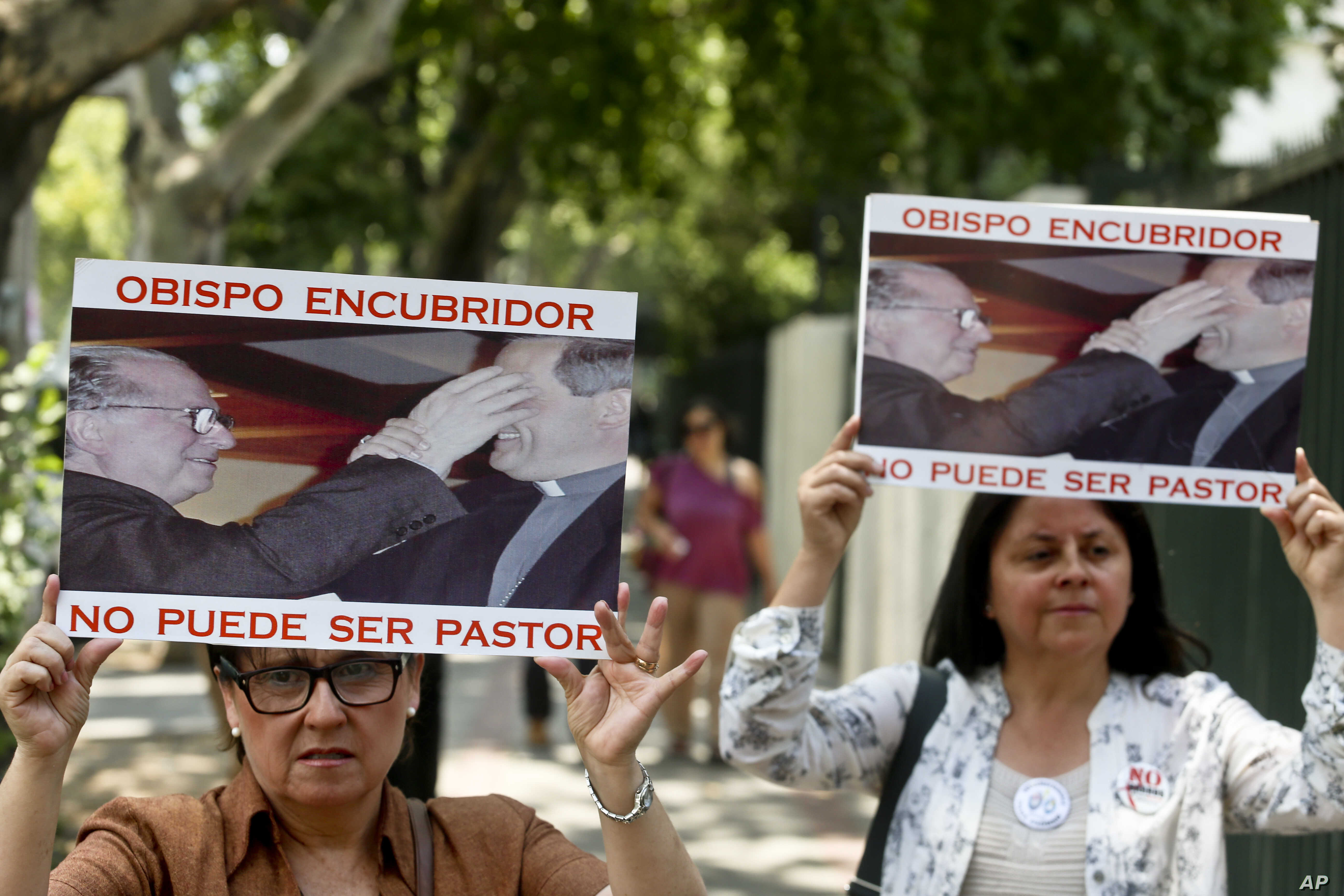 """Members of the movement Laicos de Osorno hold images of the Rev. Fernando Karadima, and his protege Juan Barros, bishop of Osorno, with a message that reads in Spanish: """"A bishop who covers up cannot be a priest,"""" during a demonstration in front of t..."""