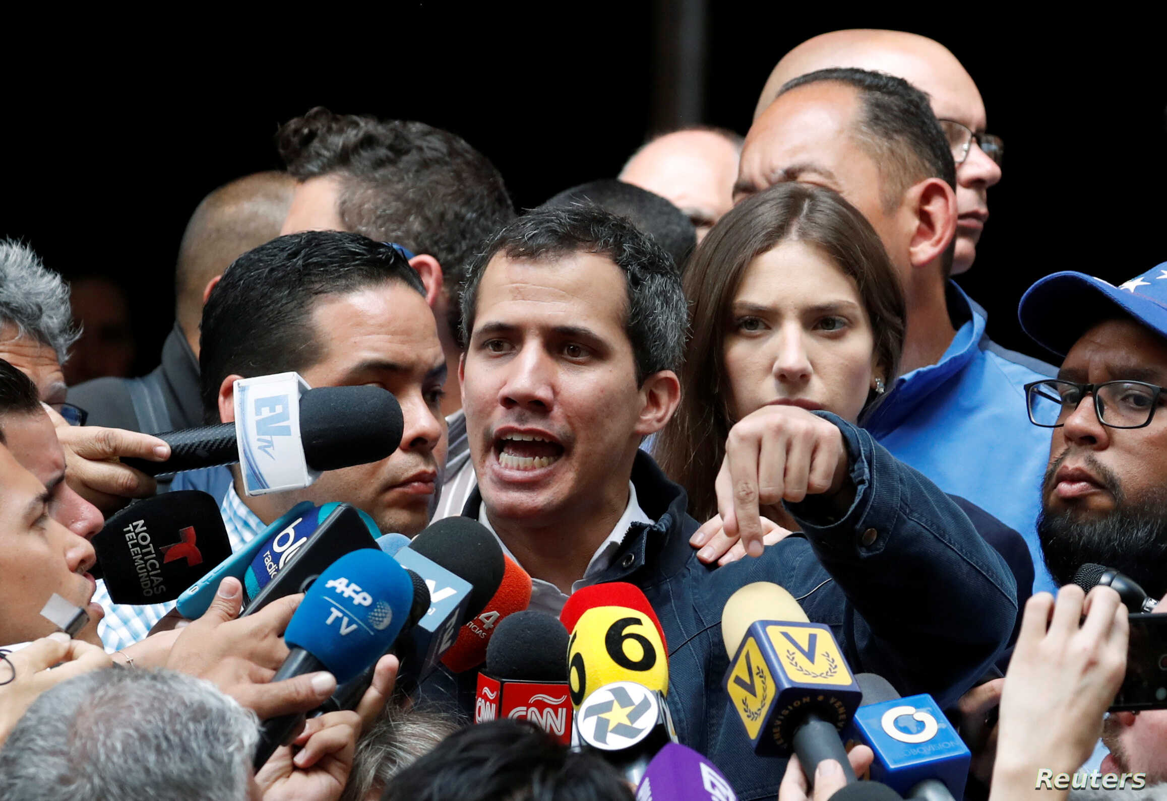 Venezuelan opposition leader and self-proclaimed interim president Juan Guaido, accompanied by his wife Fabiana Rosales, speaks to the media after a church service in Caracas, Venezuela, Jan. 27, 2019.