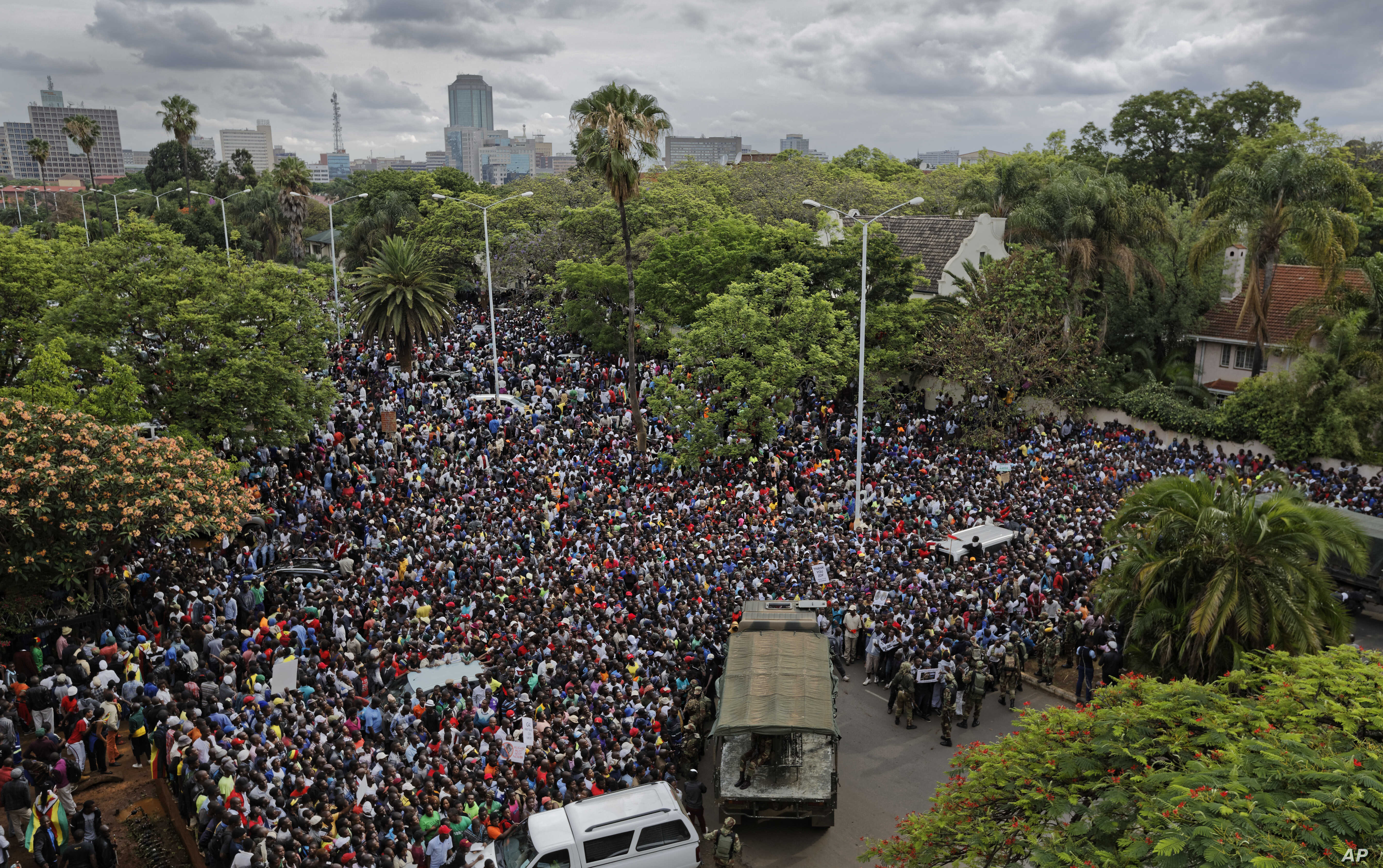 A crowd of thousands of protesters demanding President Robert Mugabe stands down gather behind an army cordon on the road leading to State House in Harare, Zimbabwe Saturday, Nov. 18, 2017.