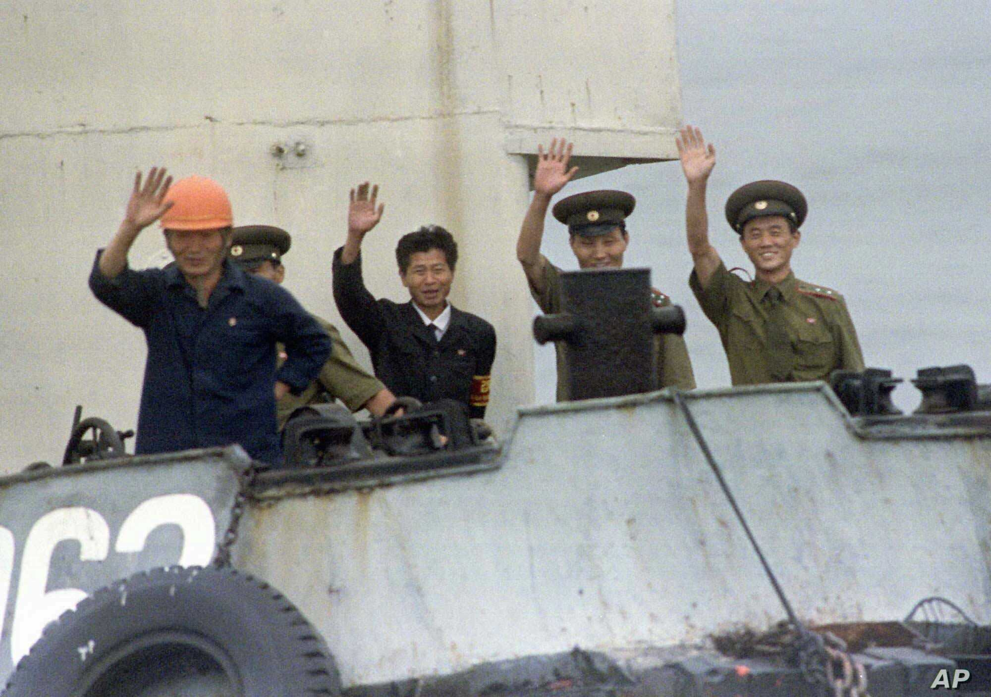 FILE - North Korean port officials wave from their launch as it approaches a South Korean ship near Yanghwa, North Korea, Aug. 19, 1997. Outsiders had been permitted to enter North Korea to attend a groundbreaking for construction of two light water ...