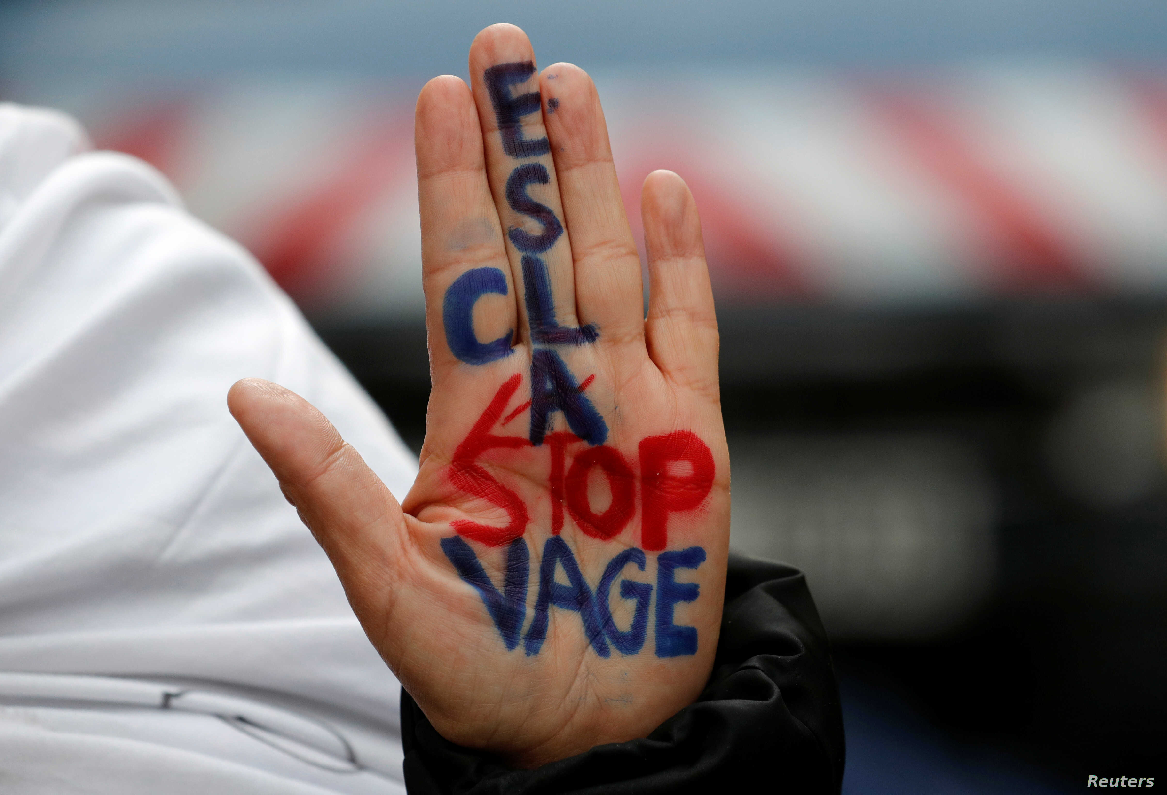"""A woman displays her hand with the message """"Stop slavery"""" as she attends a protest against slavery in Libya outside the Libyan Embassy in Paris, France, Nov. 24, 2017."""